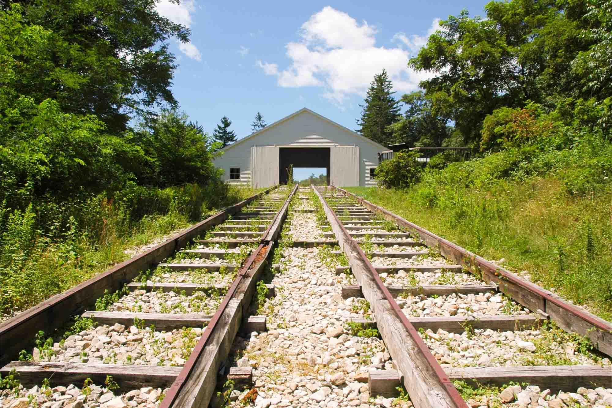 Railroad tracks leading to a barn