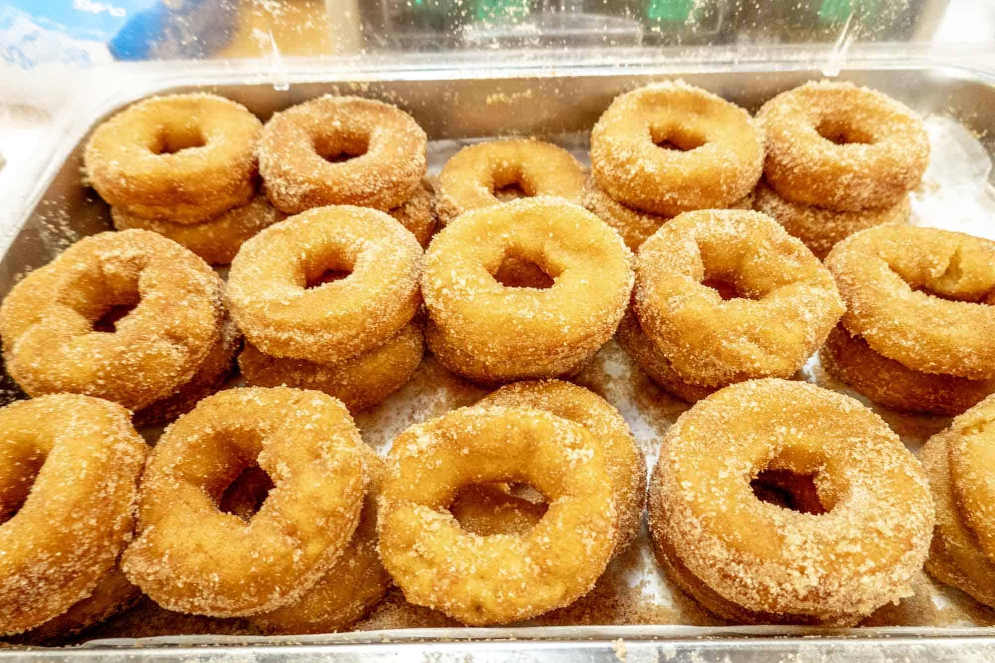 Tray full of dozens of sugar-coated donuts