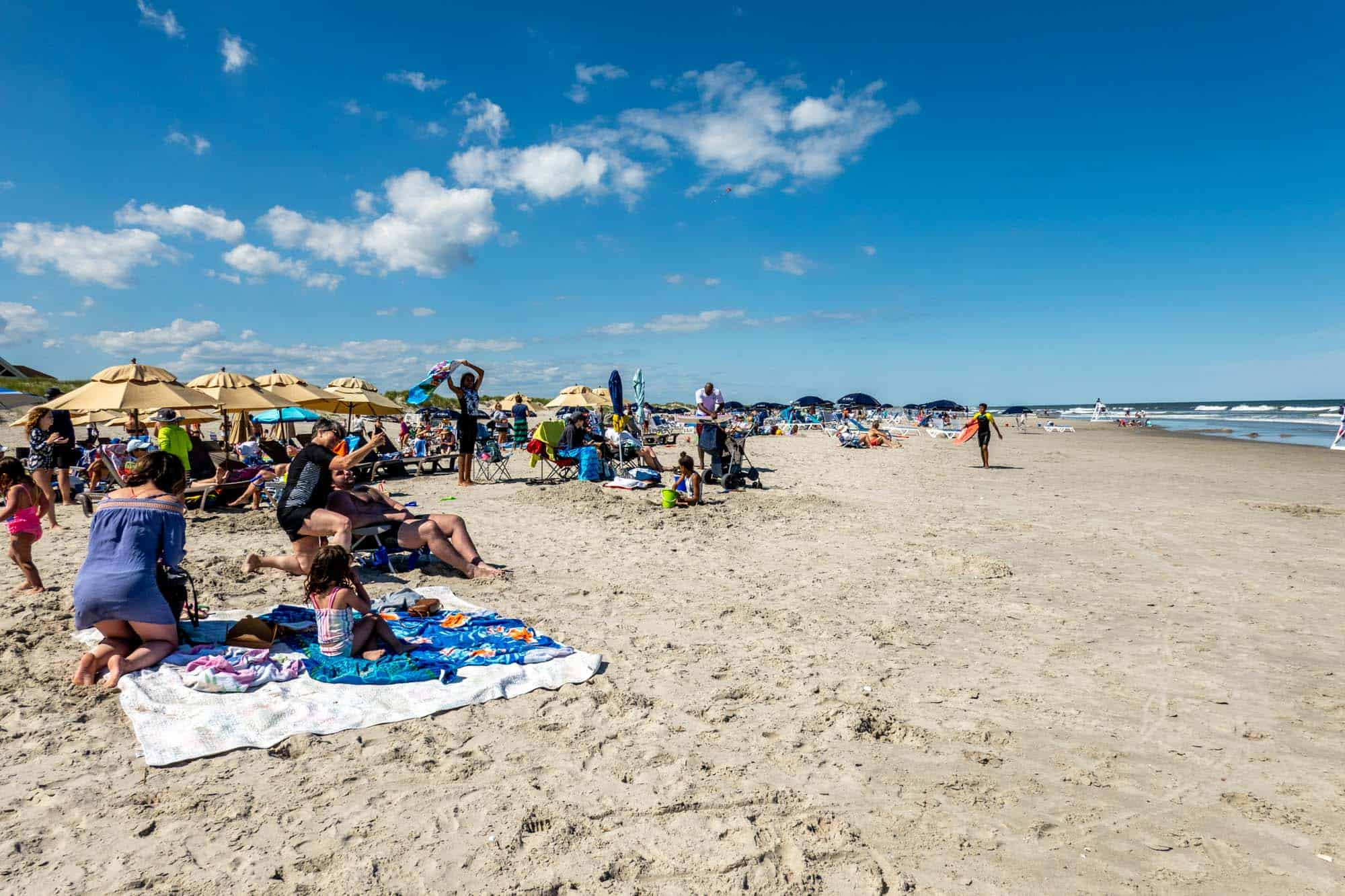 People sitting on towels and in chairs at the beach in Avalon NJ