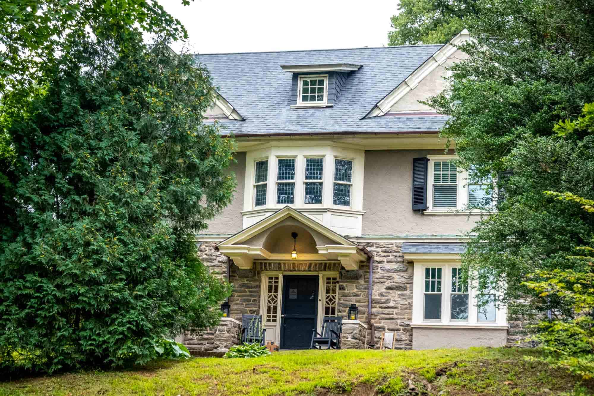 Large house made of stone and stucco with a bay window