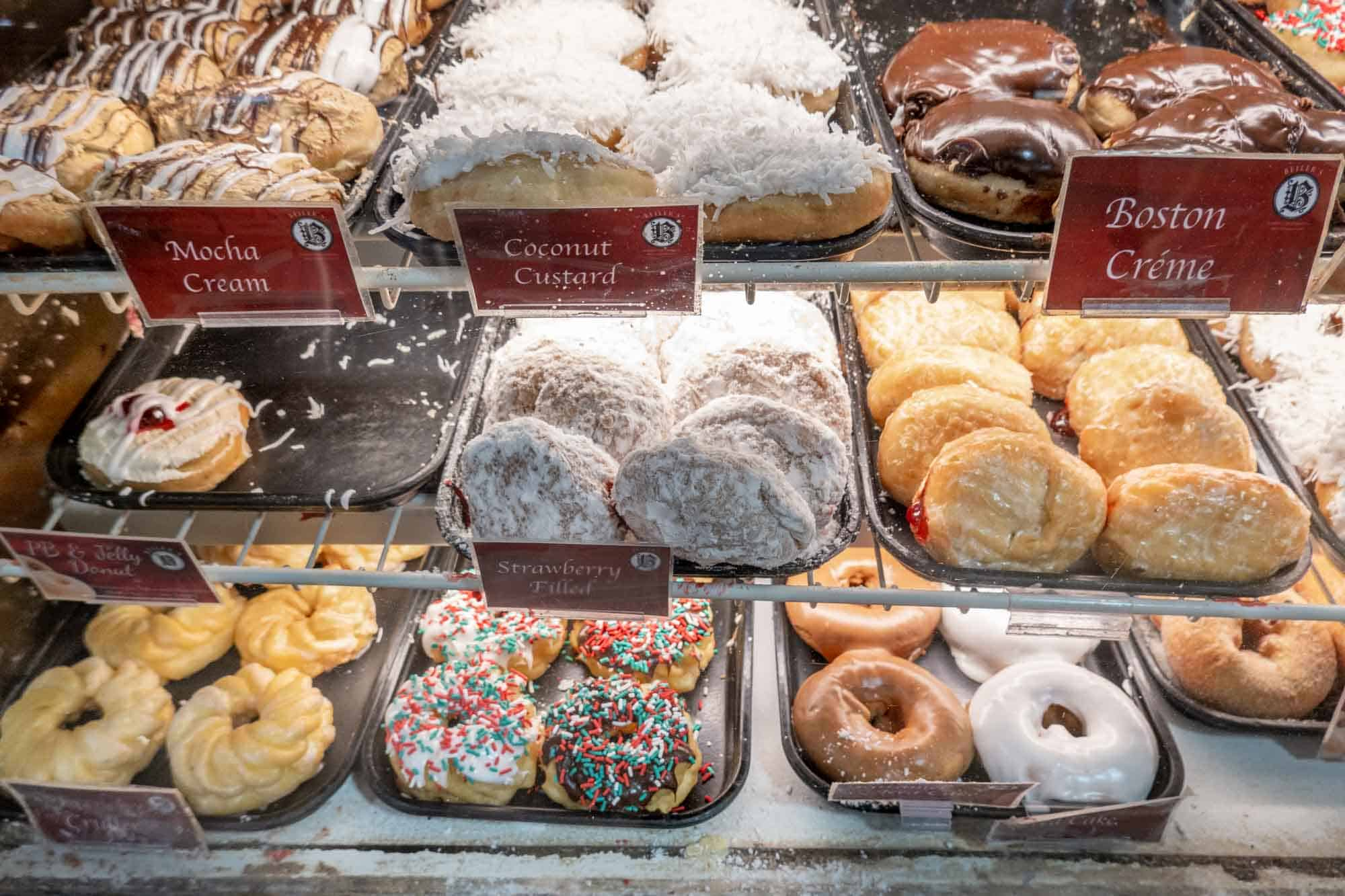Display case filled with trays of glazed and filled donuts