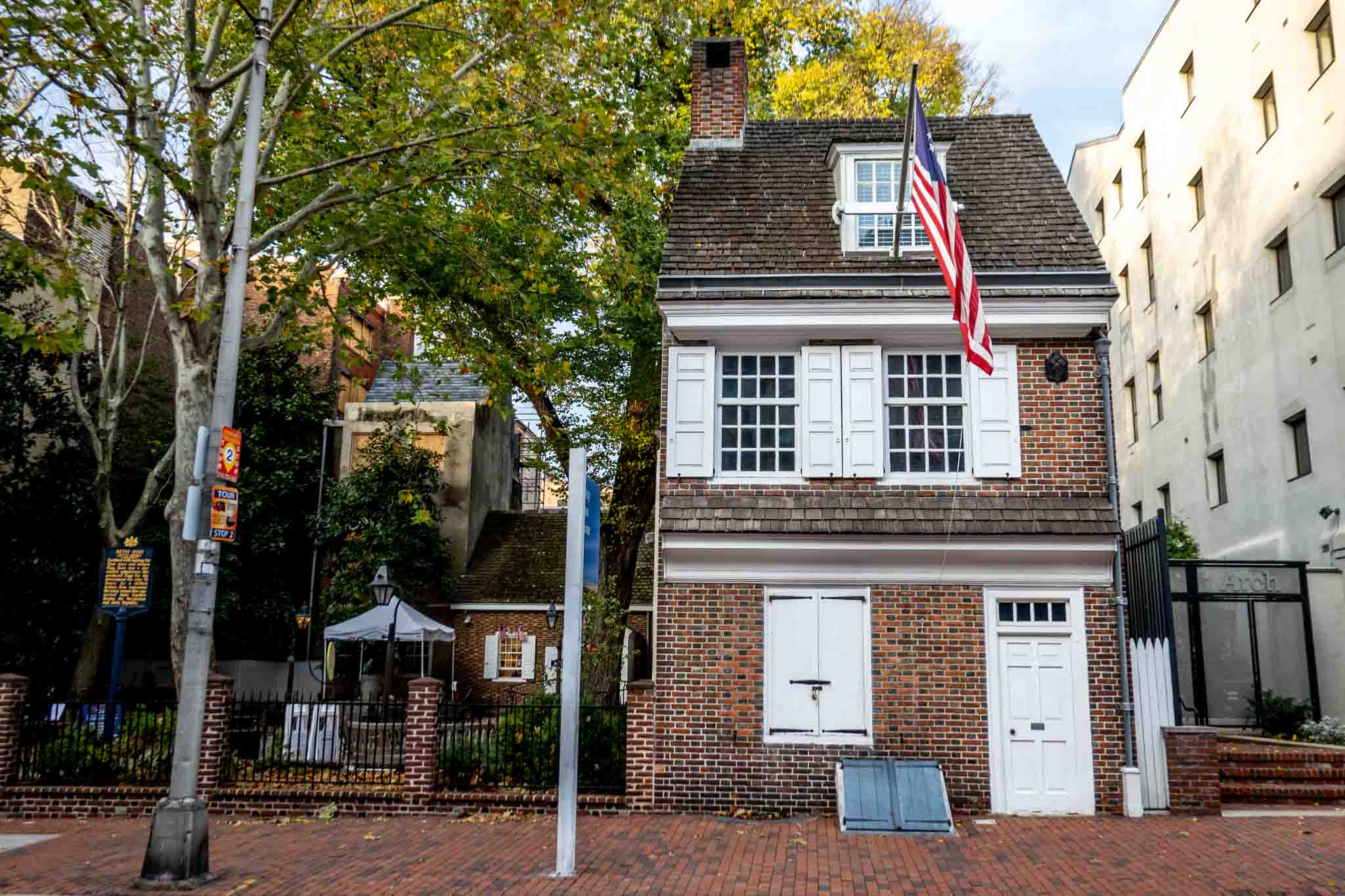 Exterior of red brick Betsy Ross House with American flag