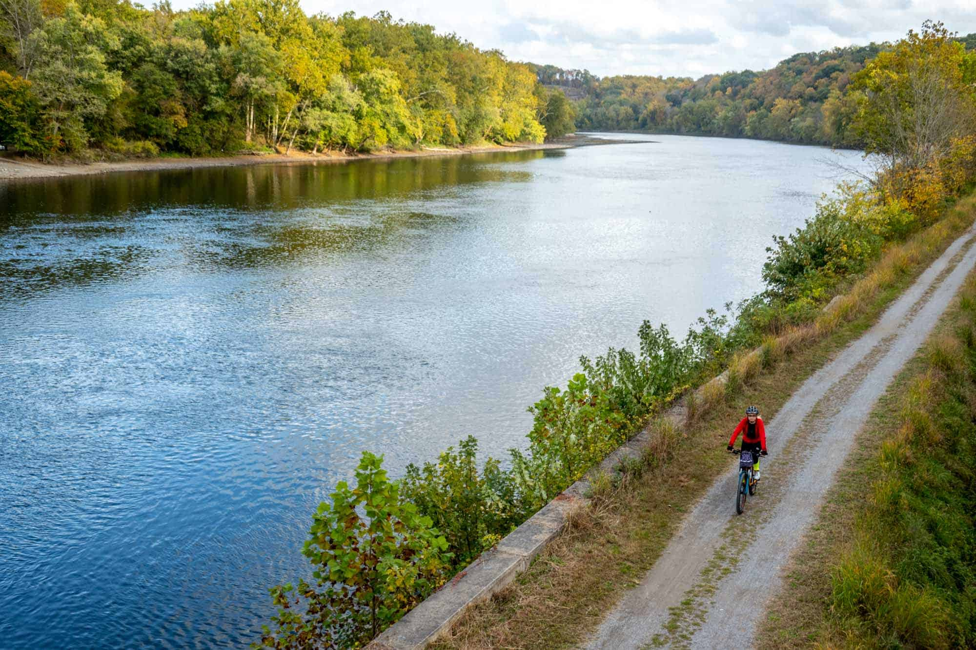 Person in a red jacket bicycling on a path beside a river