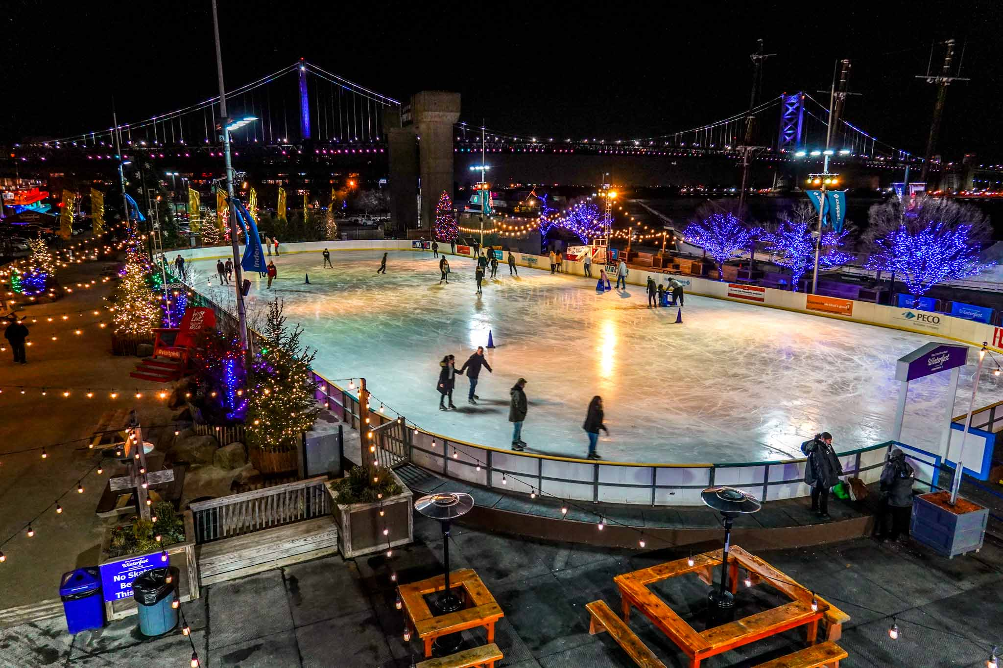 People on ice skating rink surrounded by Christmas lights