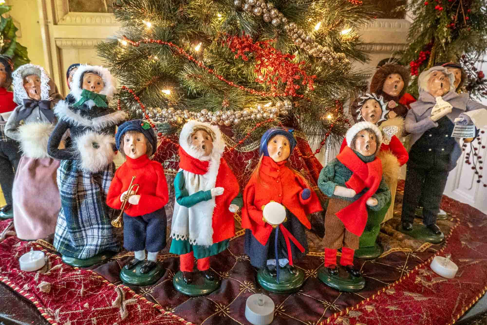 Carved wooden figurines dressed in Christmas and winter clothing