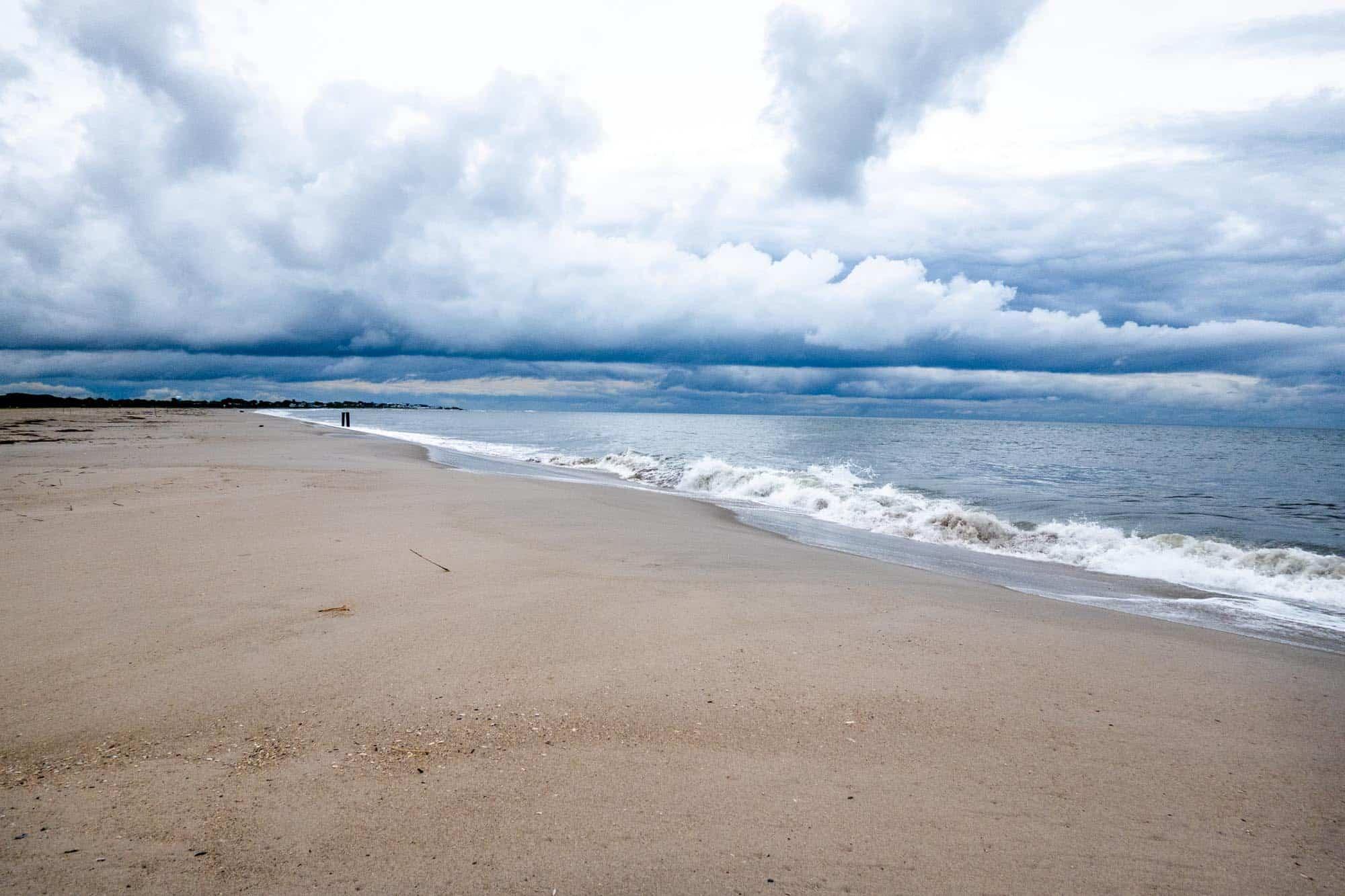 Waves crashing on sandy beach with cloudy sky