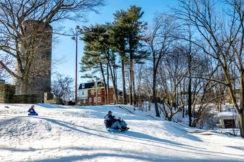 People sledding down a hill near a large stone tower