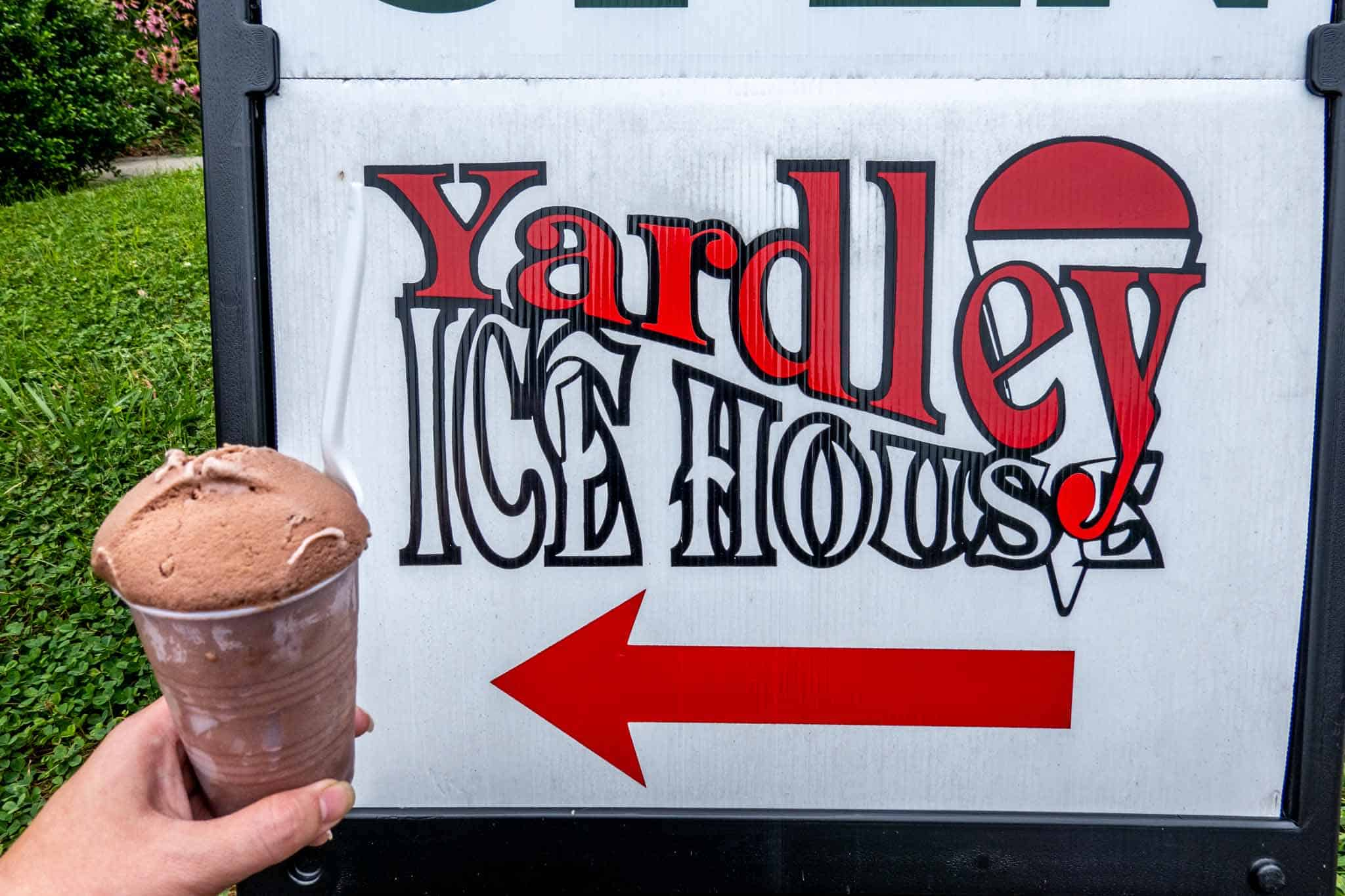 Hand holding a cup of water ice beside a sign for Yardley Ice House