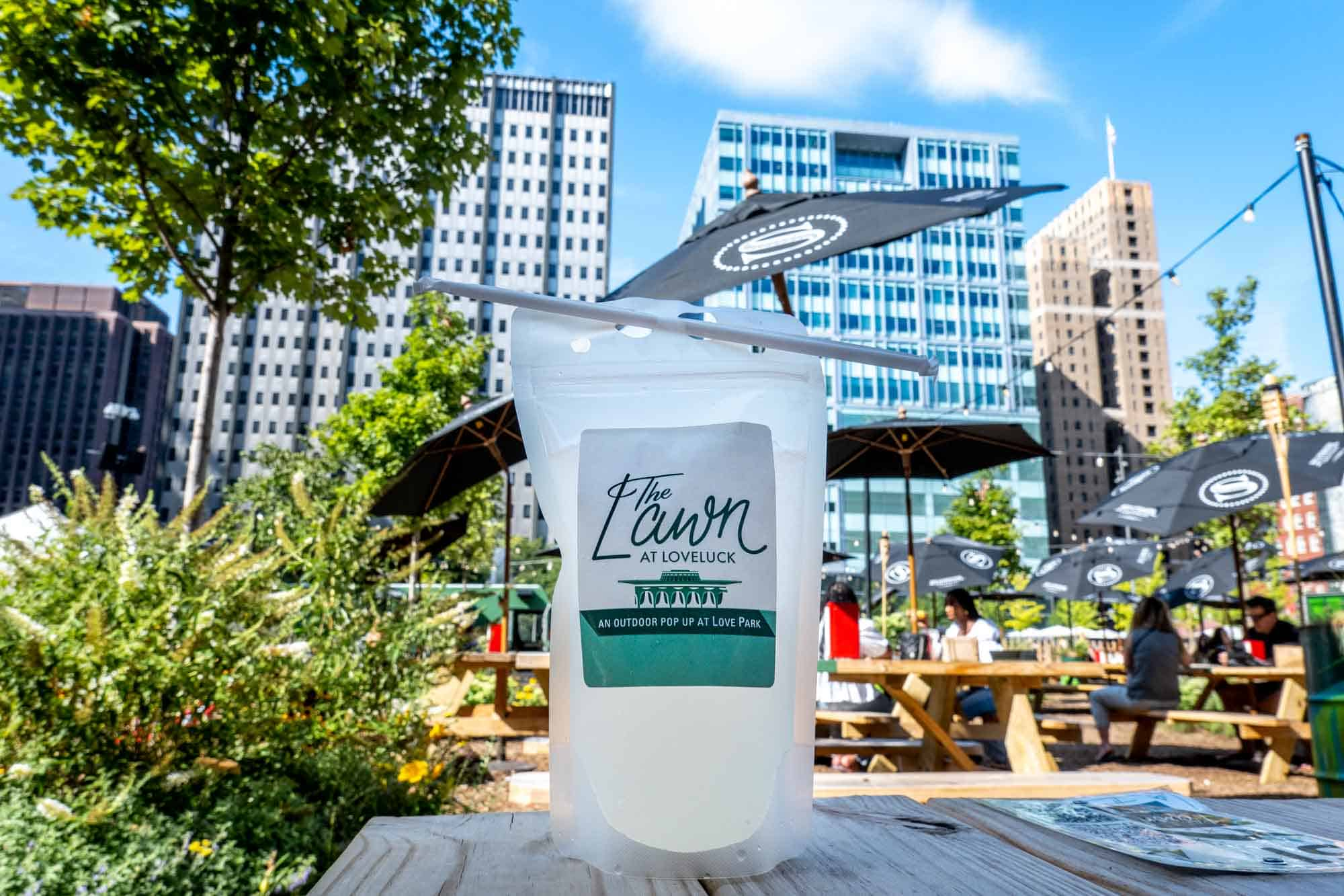"""Cocktail pouch on picnic table reading """"The Lawn at LoveLuck, an outdoor pop up at Love Park"""""""
