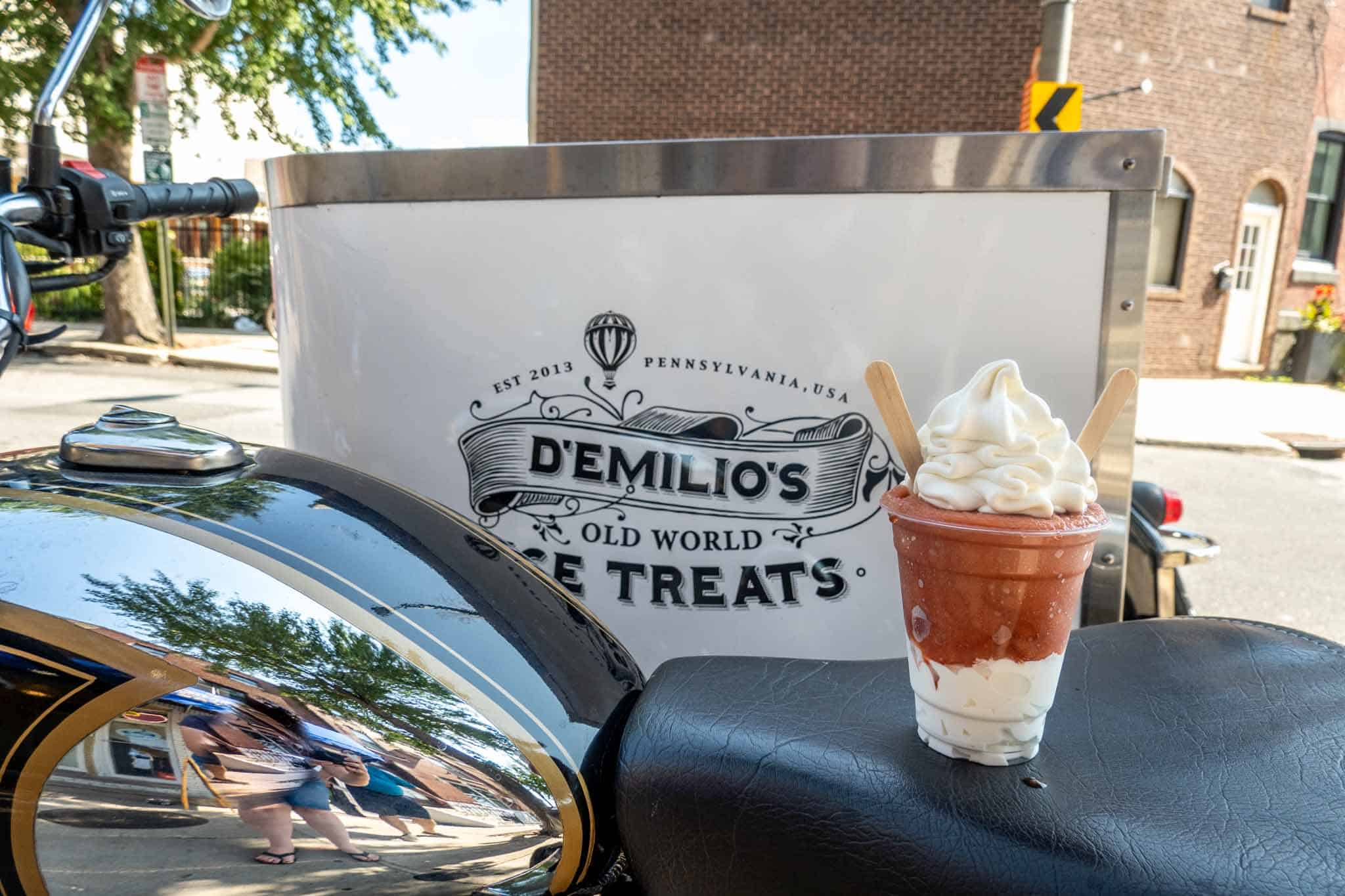 Cup filled with vanilla ice cream and birch beer water ice beside sign for D'Emilio's Old World Ice Treats