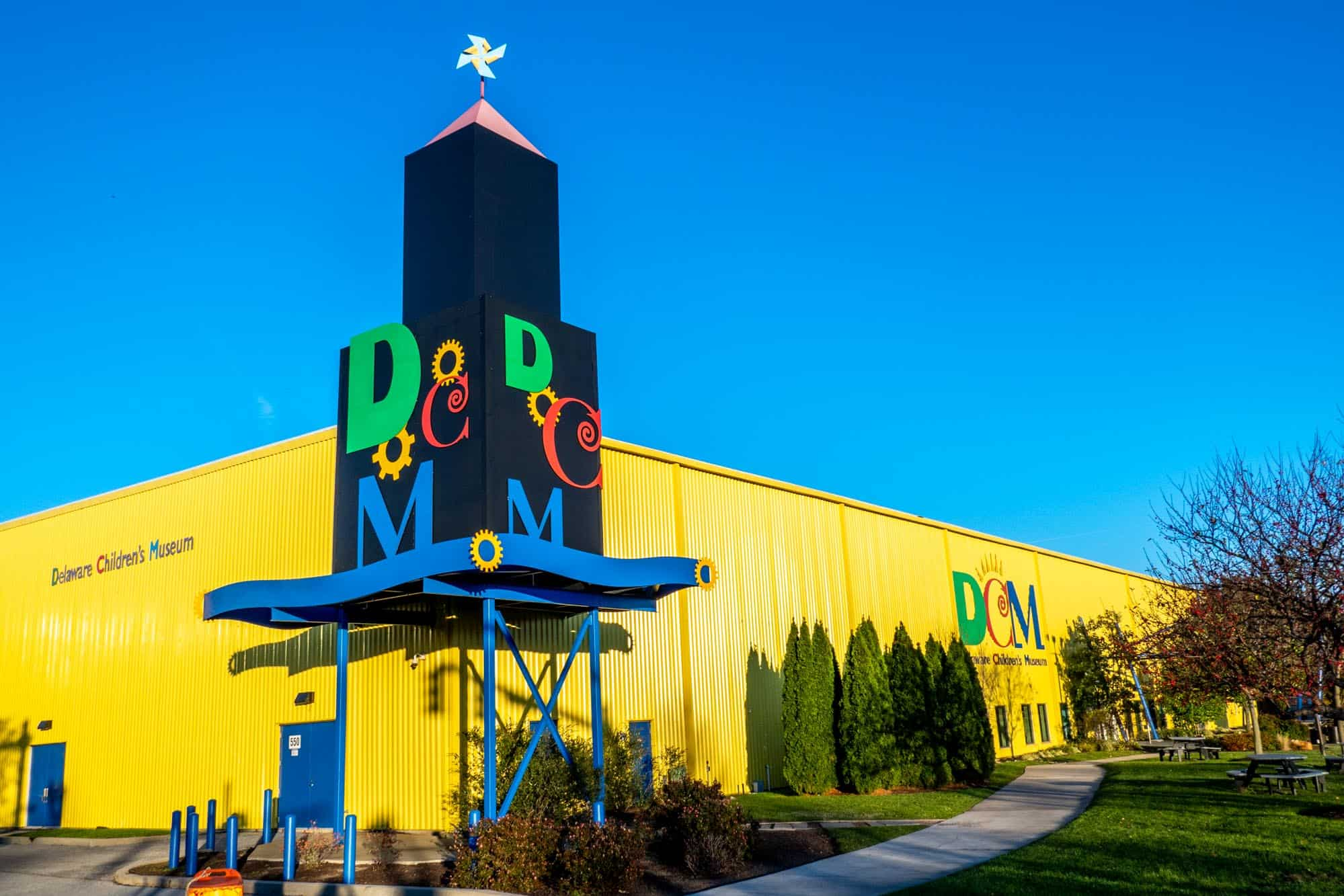 Yellow building with black, blue, red, and green details and sign for Delaware Children's Museum