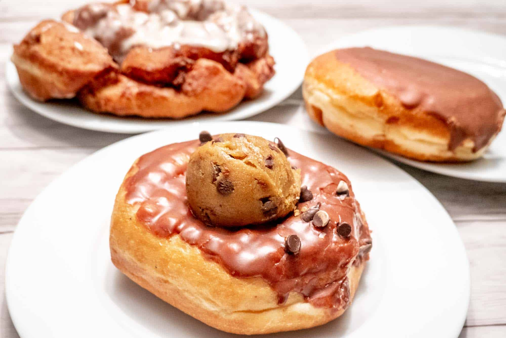 A fritter, a filled donut, and a donut topped with cookie dough on three plates