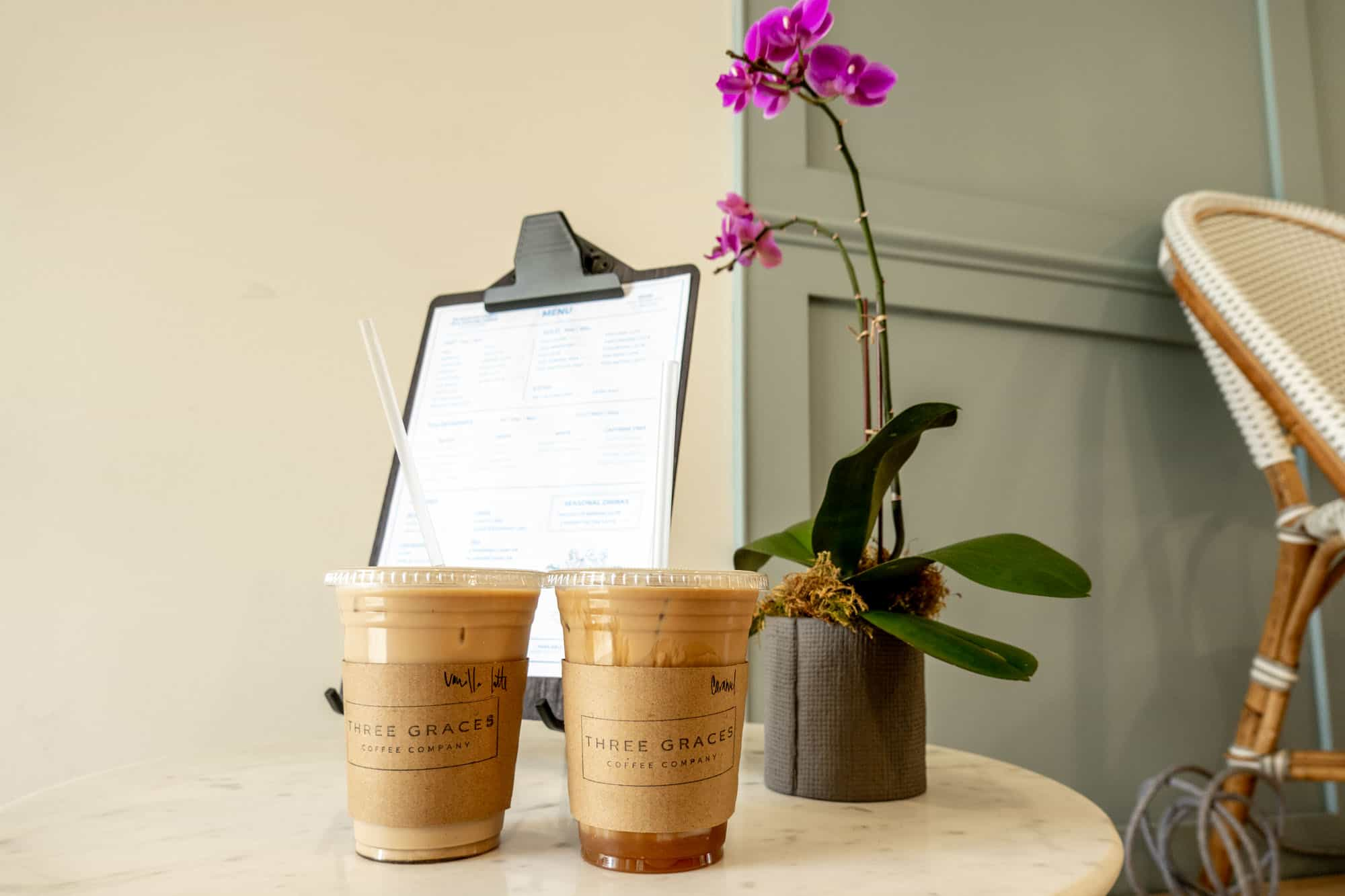 """Two plastic cups of ice coffee on a table with sleeves labeled for """"Three Graces Coffee Co."""""""