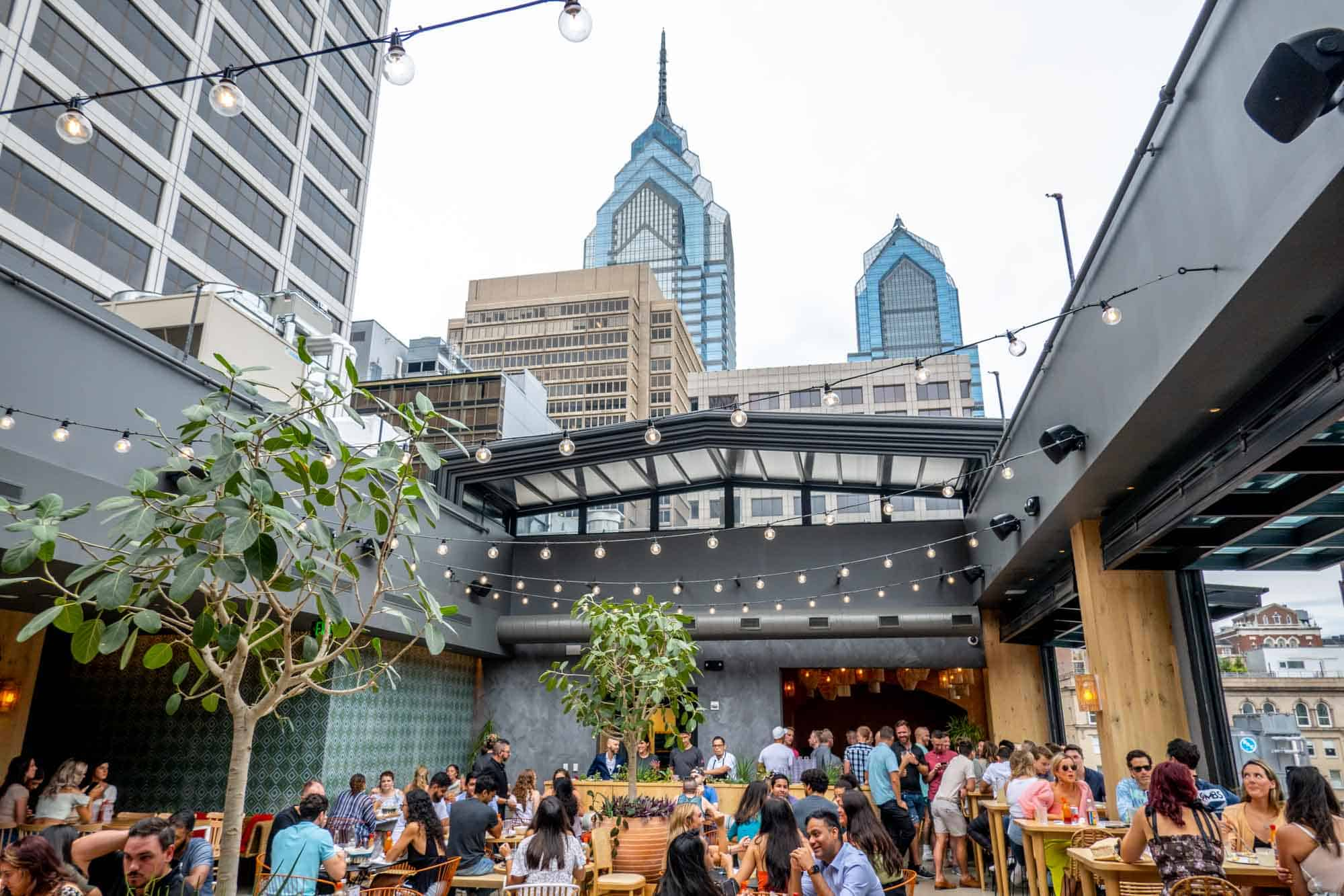City buildings towering above a rooftop restaurant with a retractable roof where people are eating