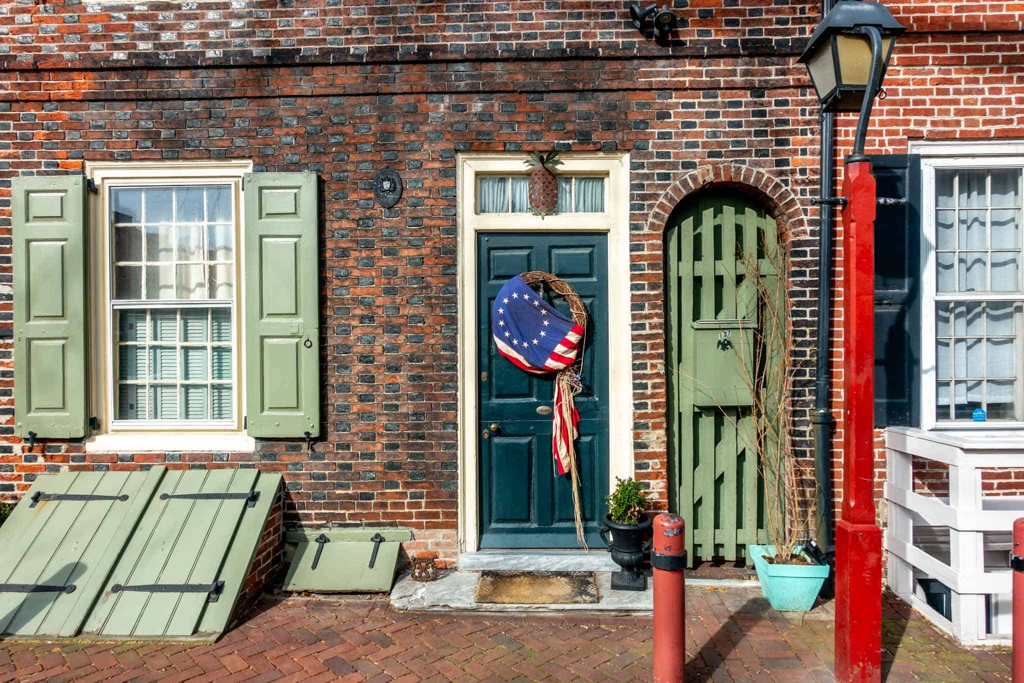 Entrance to home in Elfreth's Alley with green door, shutters, and a wreath covered with the colonial American flag