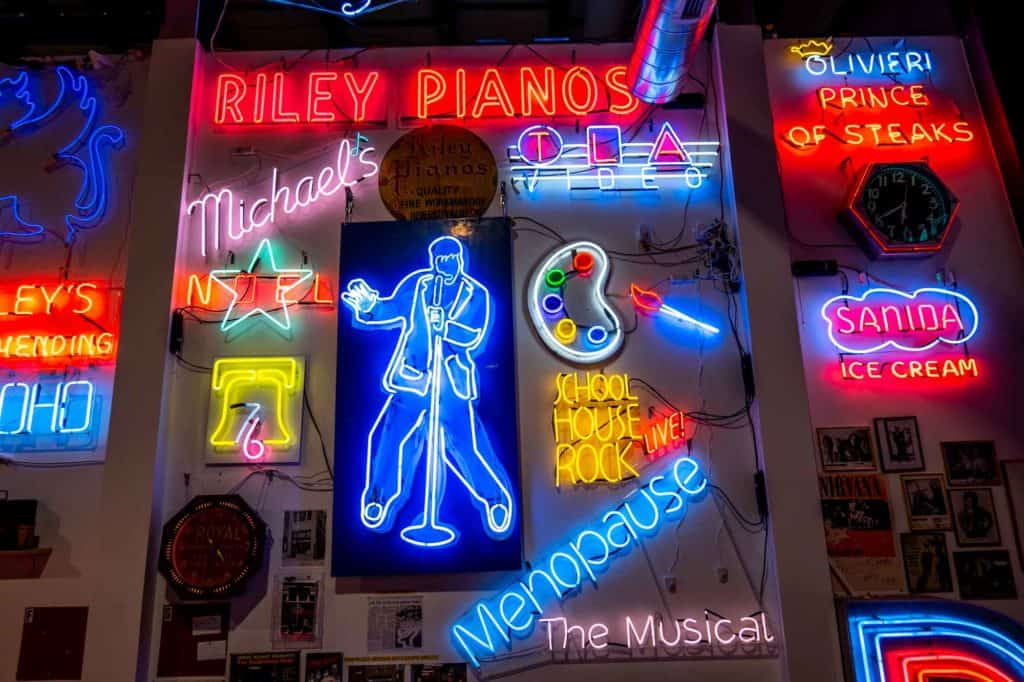 """Colorful neon signs on a wall, including an image of Elvis, a painters' palette, and """"School House Rock Live!"""""""