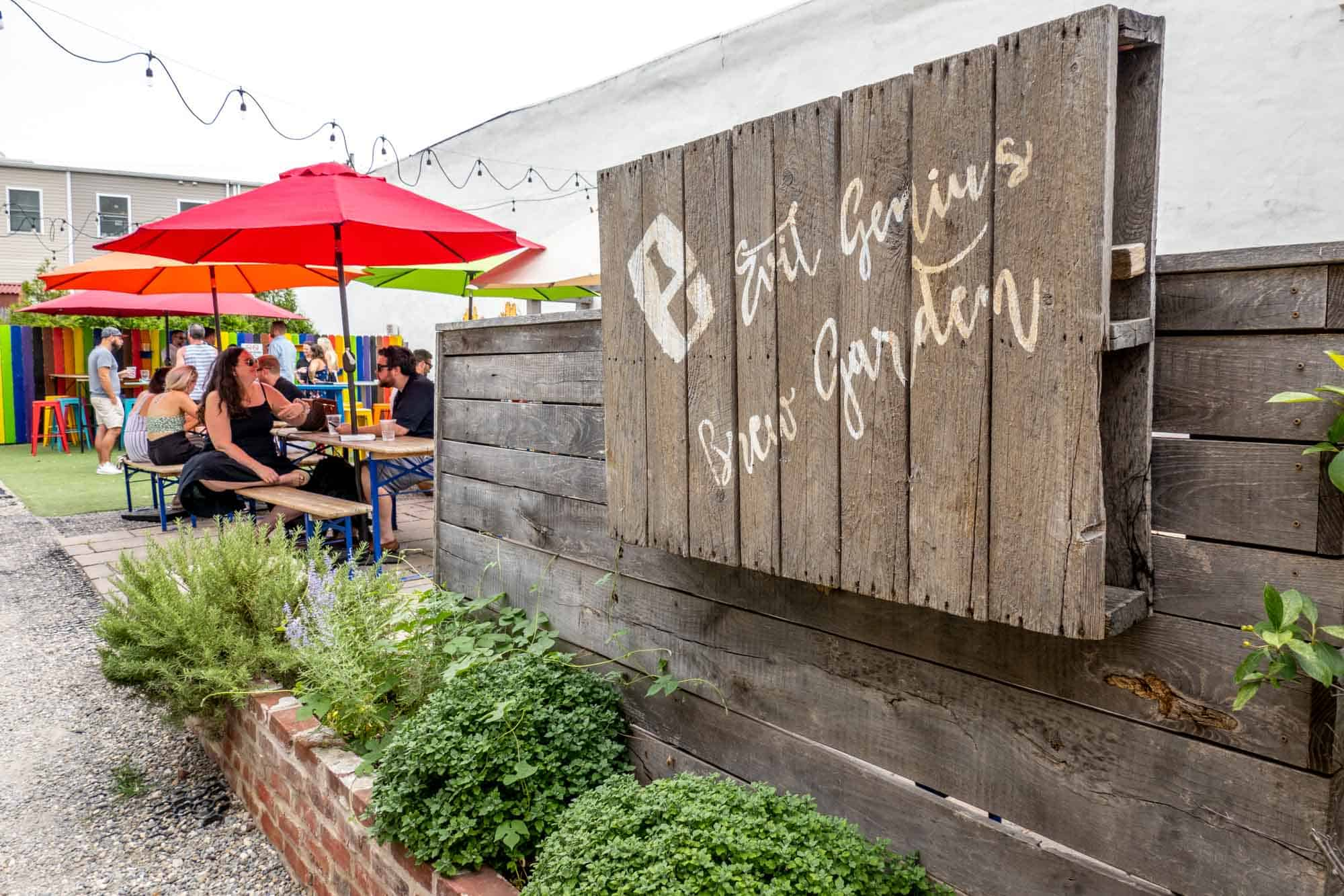 """Sign reading """"Evil Genius beer garden"""" in front of tables with colorful umbrellas"""