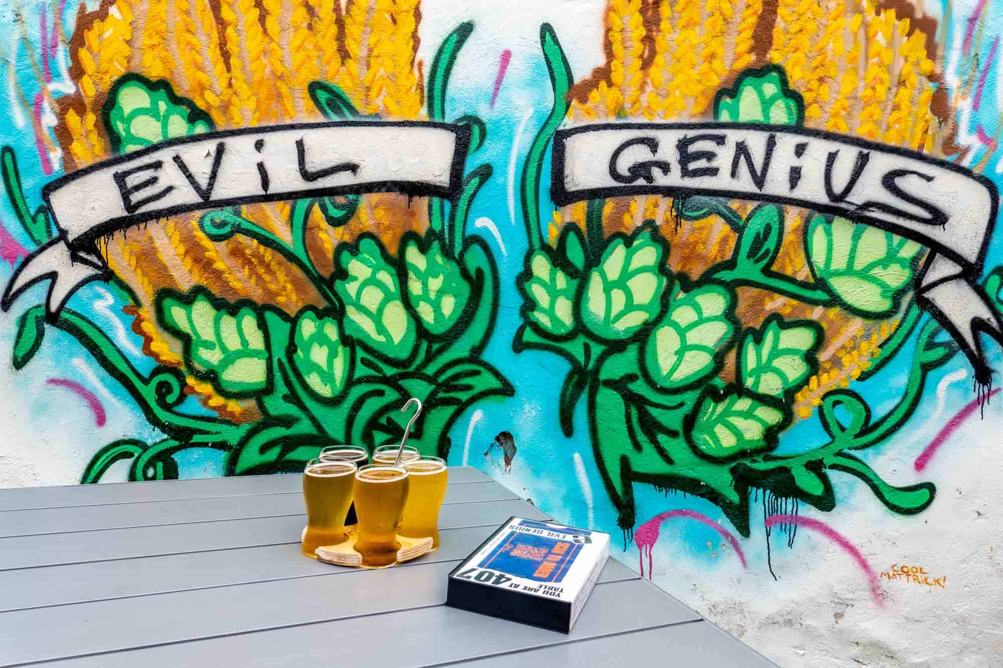 Beer tasting flight on table in front of Evil Genius mural