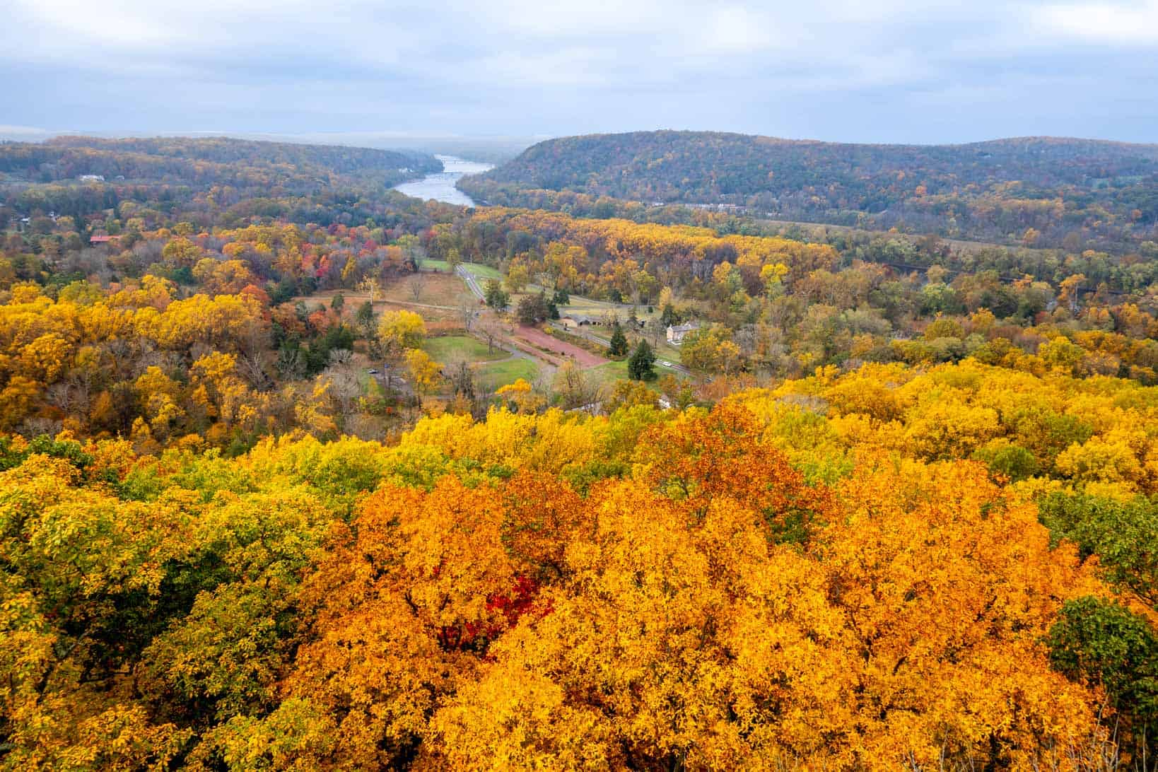 Aerial view of a landscape filled with fall foliage and a river cutting through it