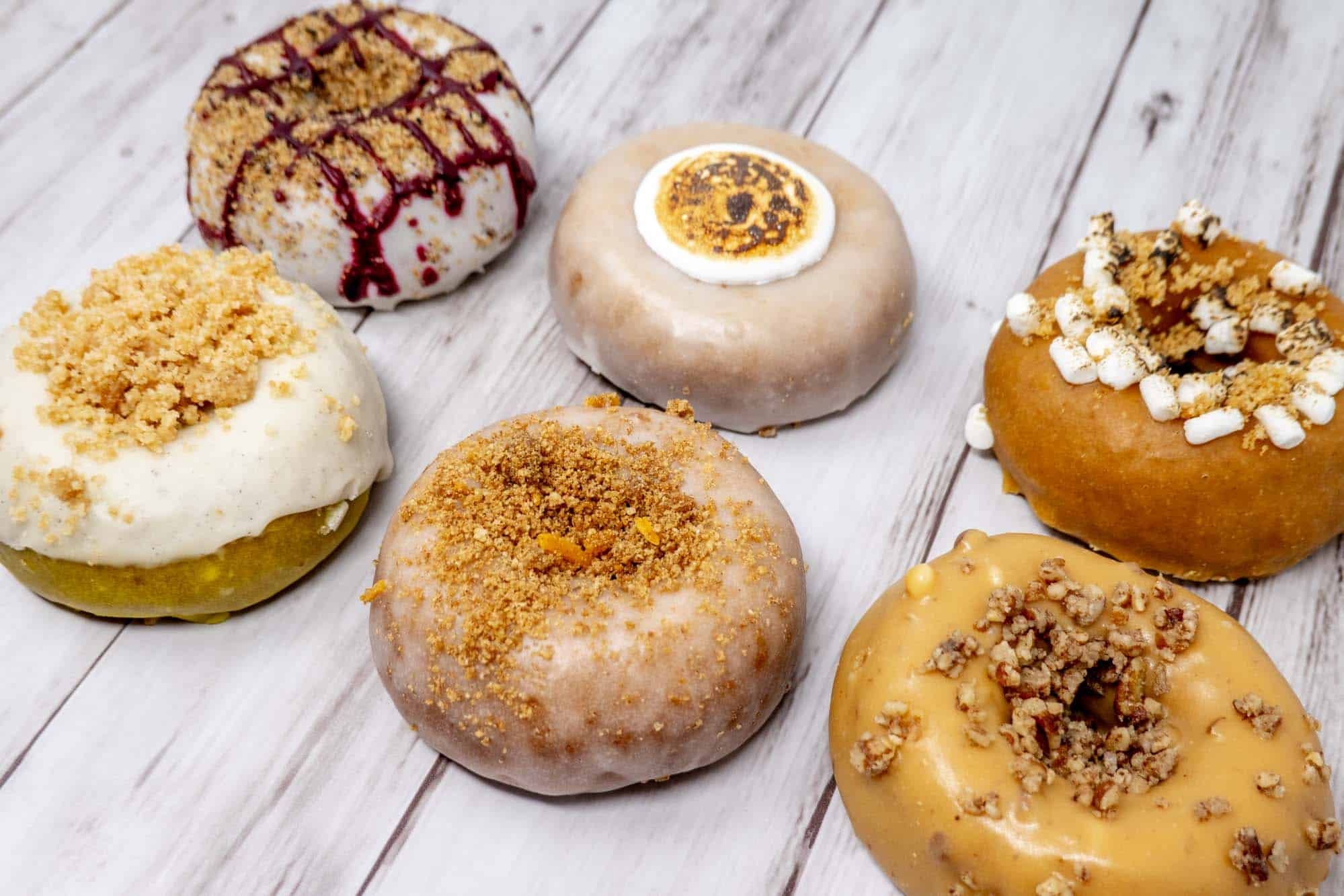 Six donuts with different flavors and toppings on a table