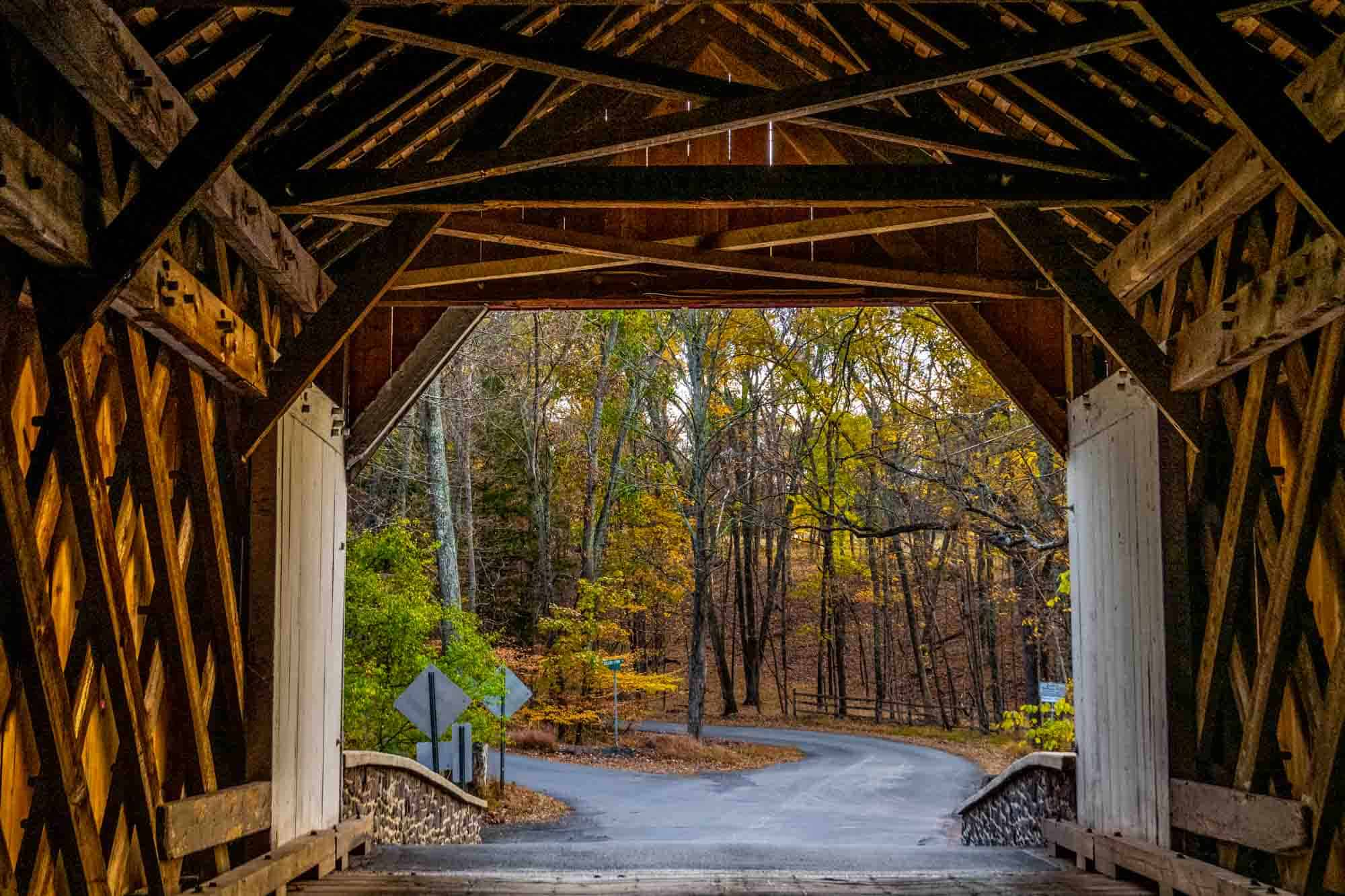 View of a road and trees from inside a wooden covered bridge