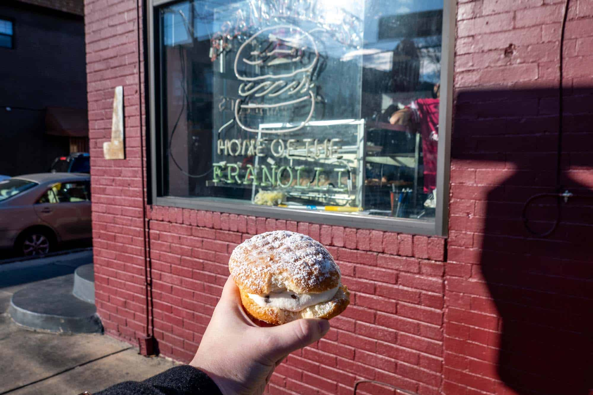 """Hand holding a pastry in front of a sign for """"Frangelli's: Home of the Franolli"""""""