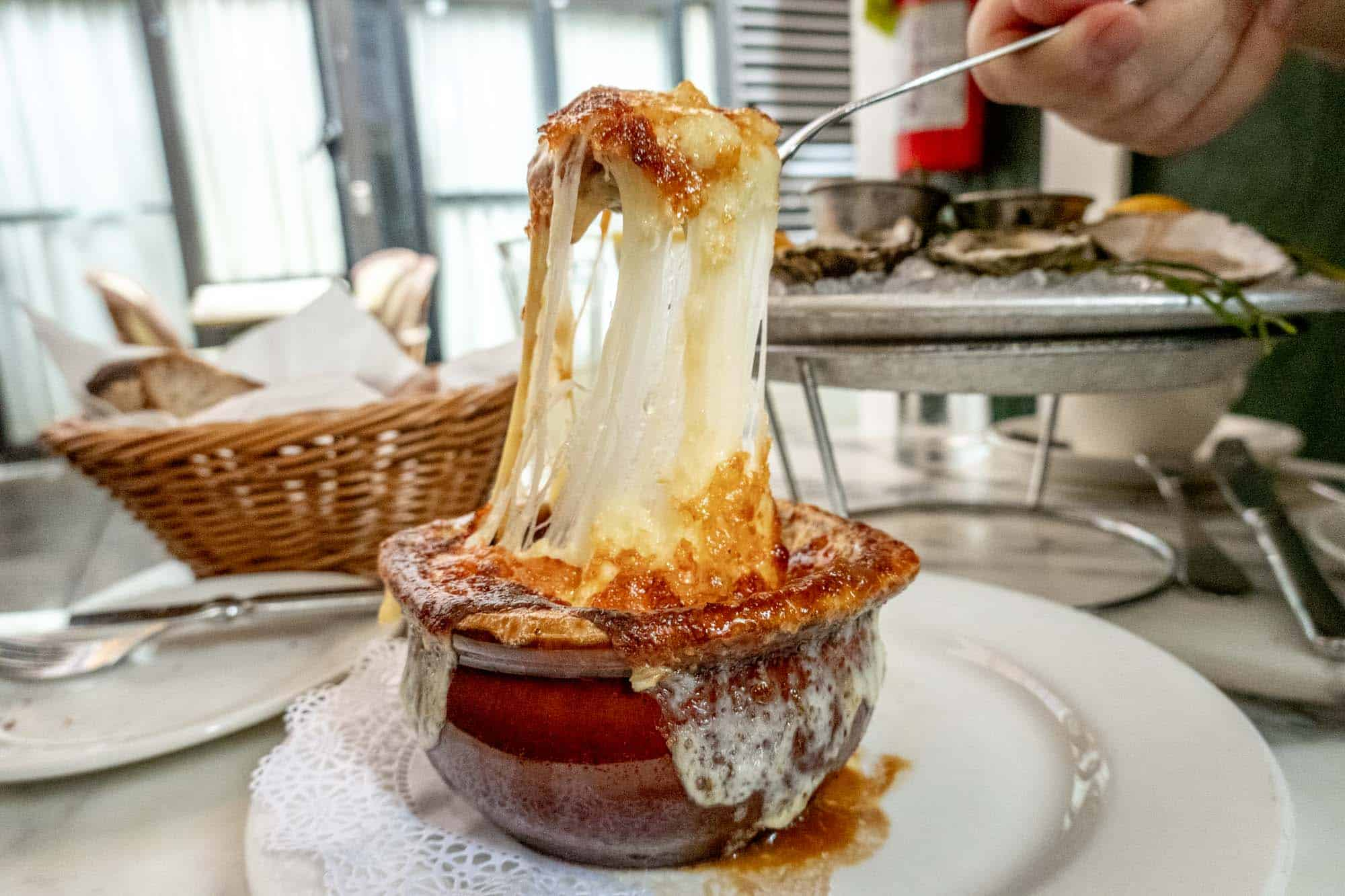 Soup bowl topped with melted cheese pulled up by a spoon