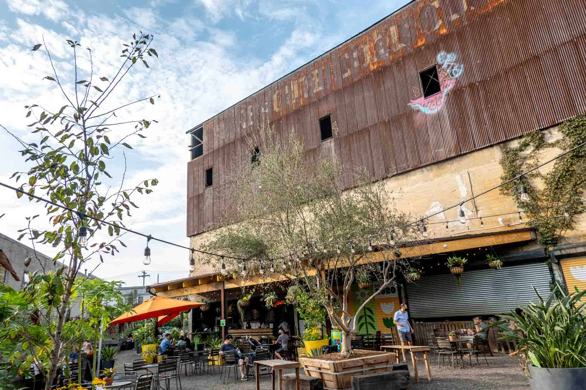 Beer garden at base of rusted, abandoned industrial building