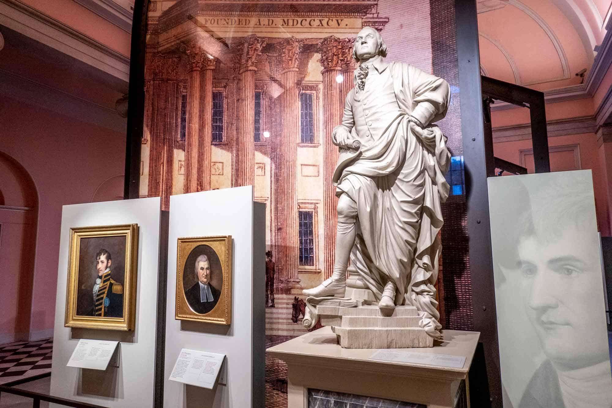 Statue of George Washington beside portraits of men