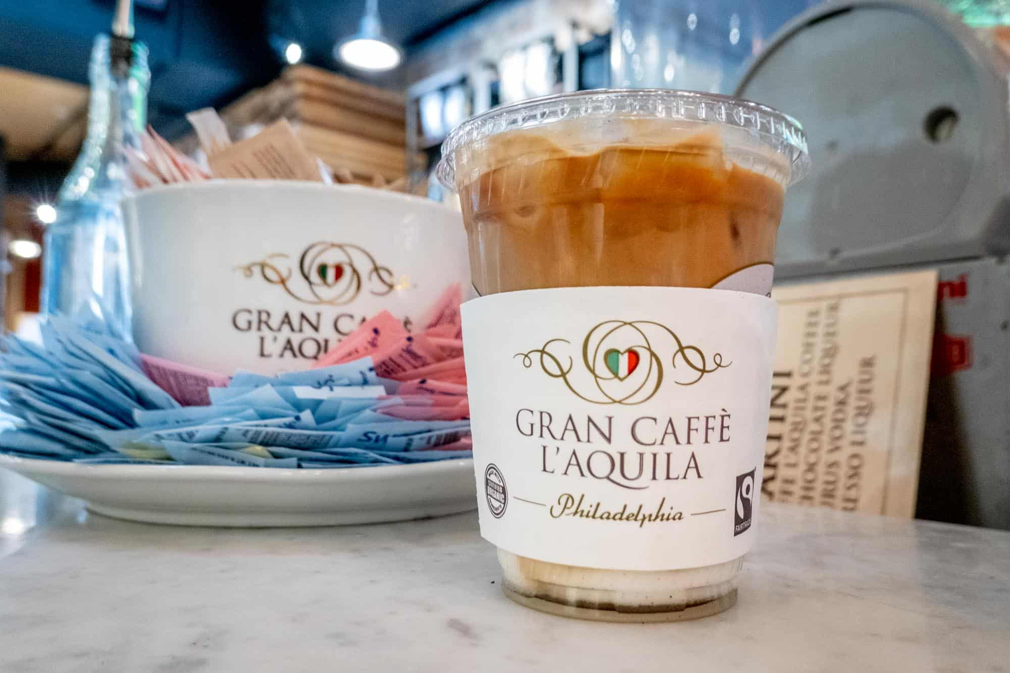 """Cup of iced coffee on a counter with a sleeve labeled """"Gran Caffe L'Aquila: Philadelphia"""""""