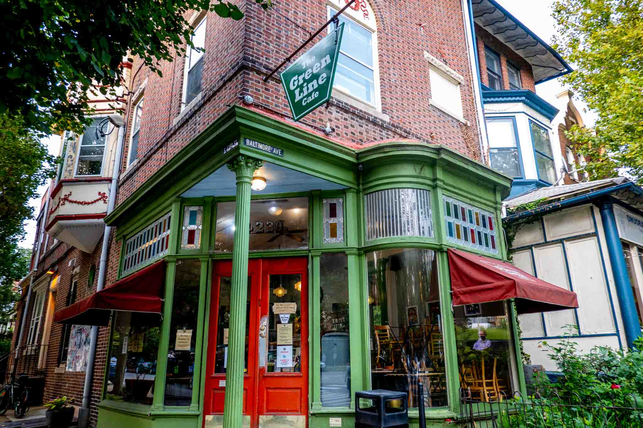"""Exterior of a cafe painted red and green with a sign for """"The Green Line Cafe"""""""