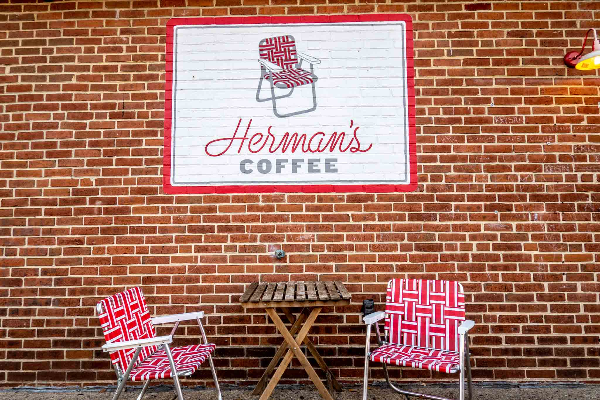 """Red lawn chairs under sign for """"Herman's Coffee"""""""