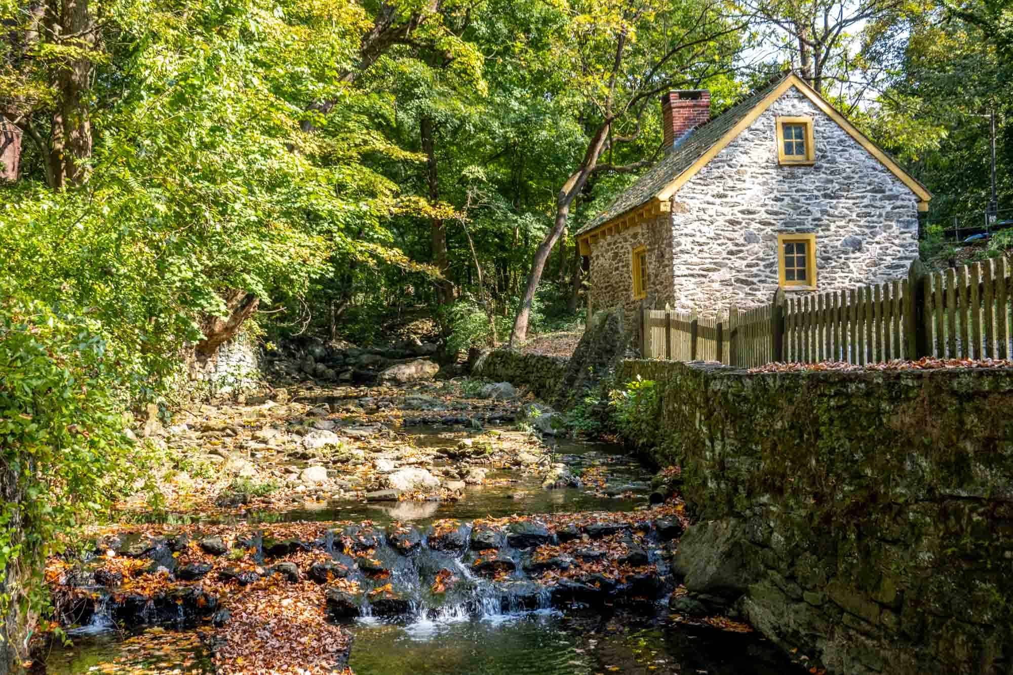 Stone building beside a small waterfall with fall leaves scatter4ed around
