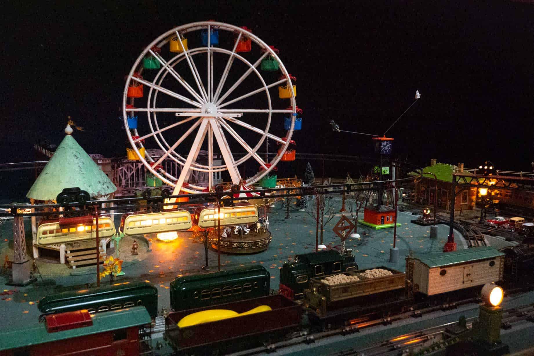 Miniature train circling a carnival scene