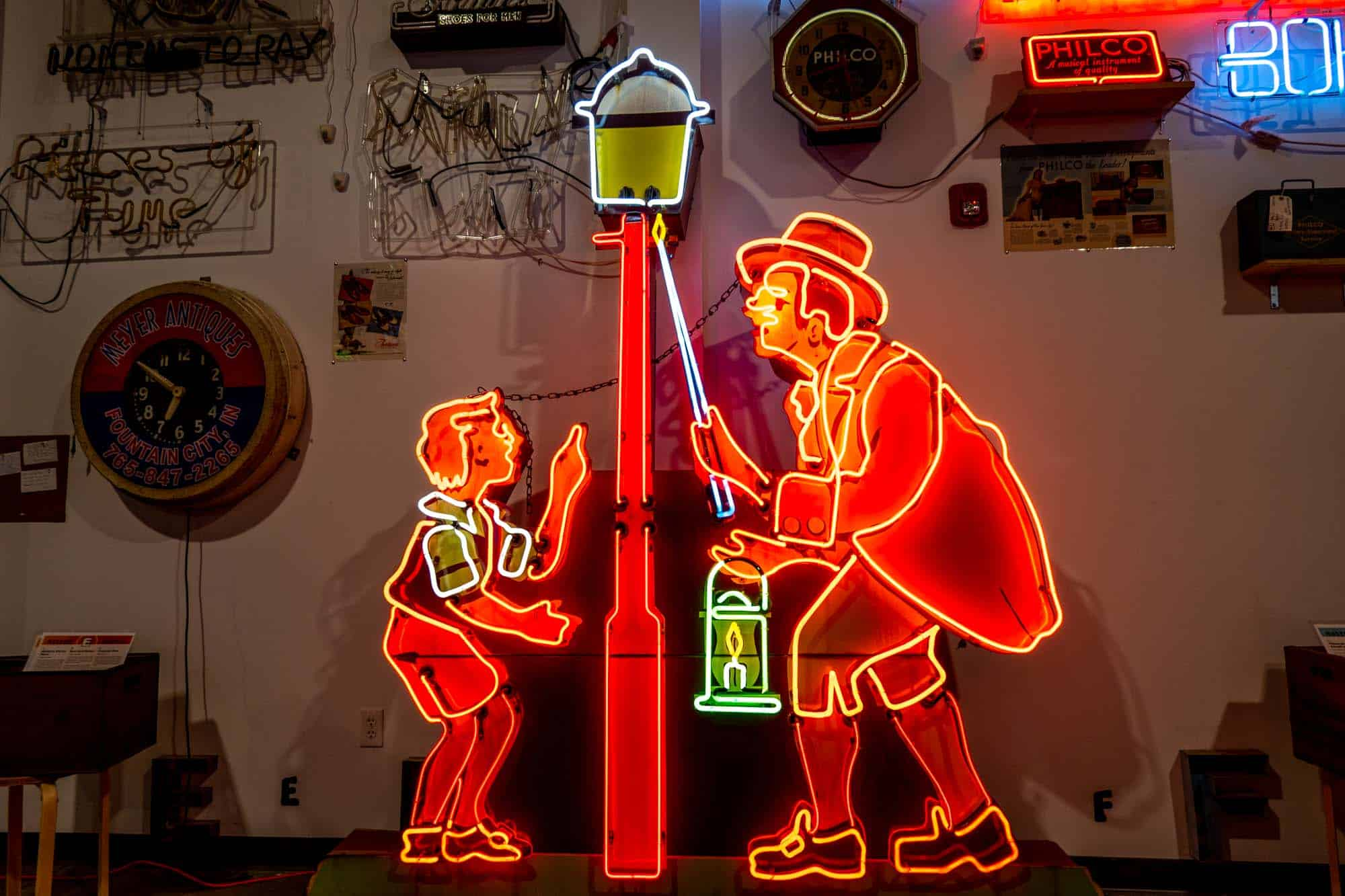 Large red neon sign showing a man lighting a street lamp beside a young boy