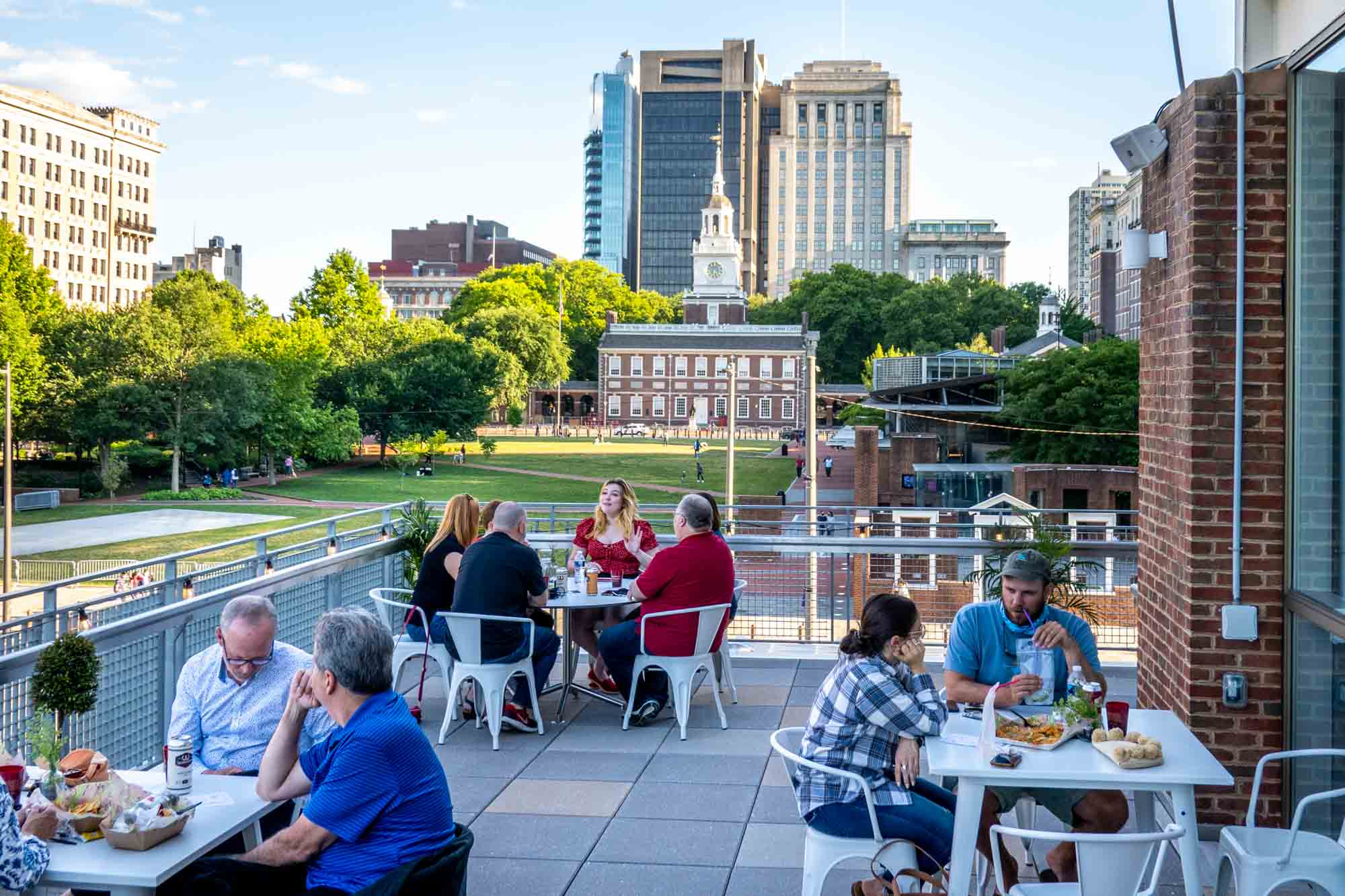 People seated at tables on an outdoor deck with a view of Independence Hall