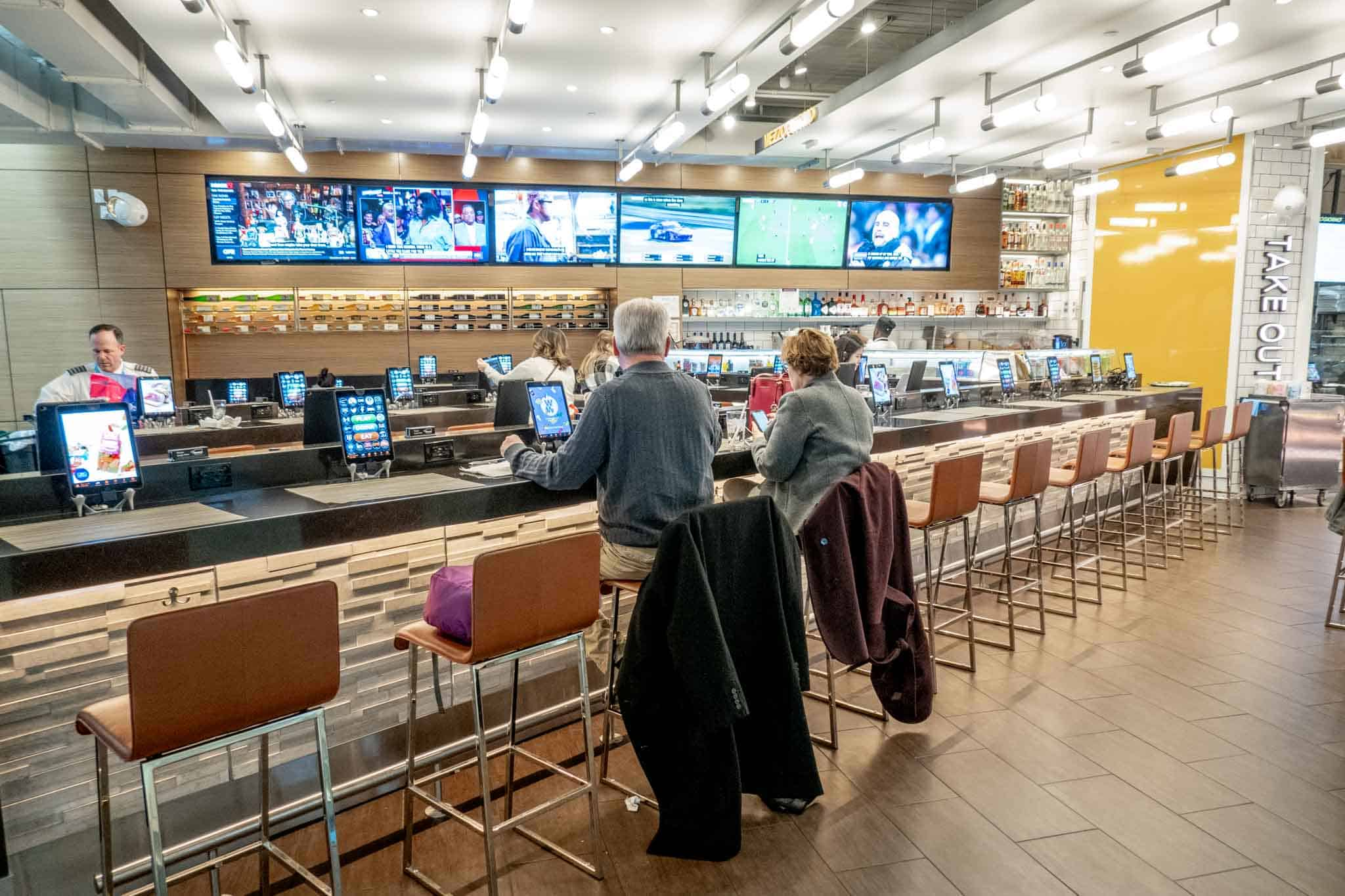People sitting at a bar at Philadelphia airport with lots of TV screens