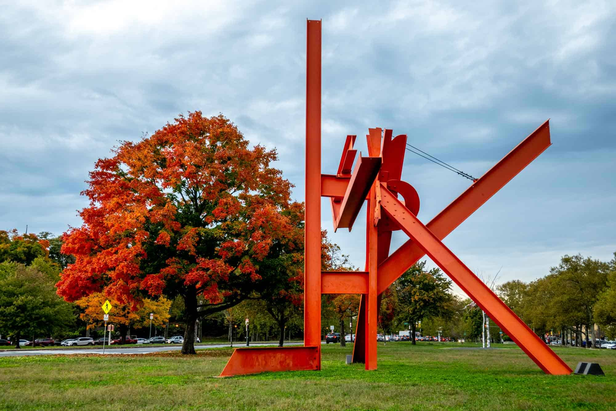 Bright red maple tree beside an abstract sculpture made from red steel