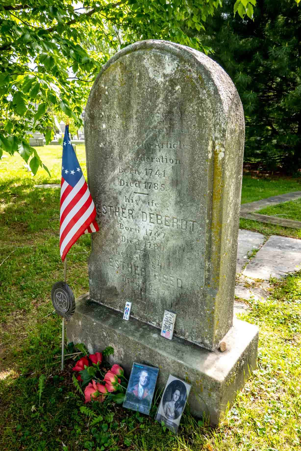 Headstone for Joseph Reed and family decorated with photos and a Colonial flag