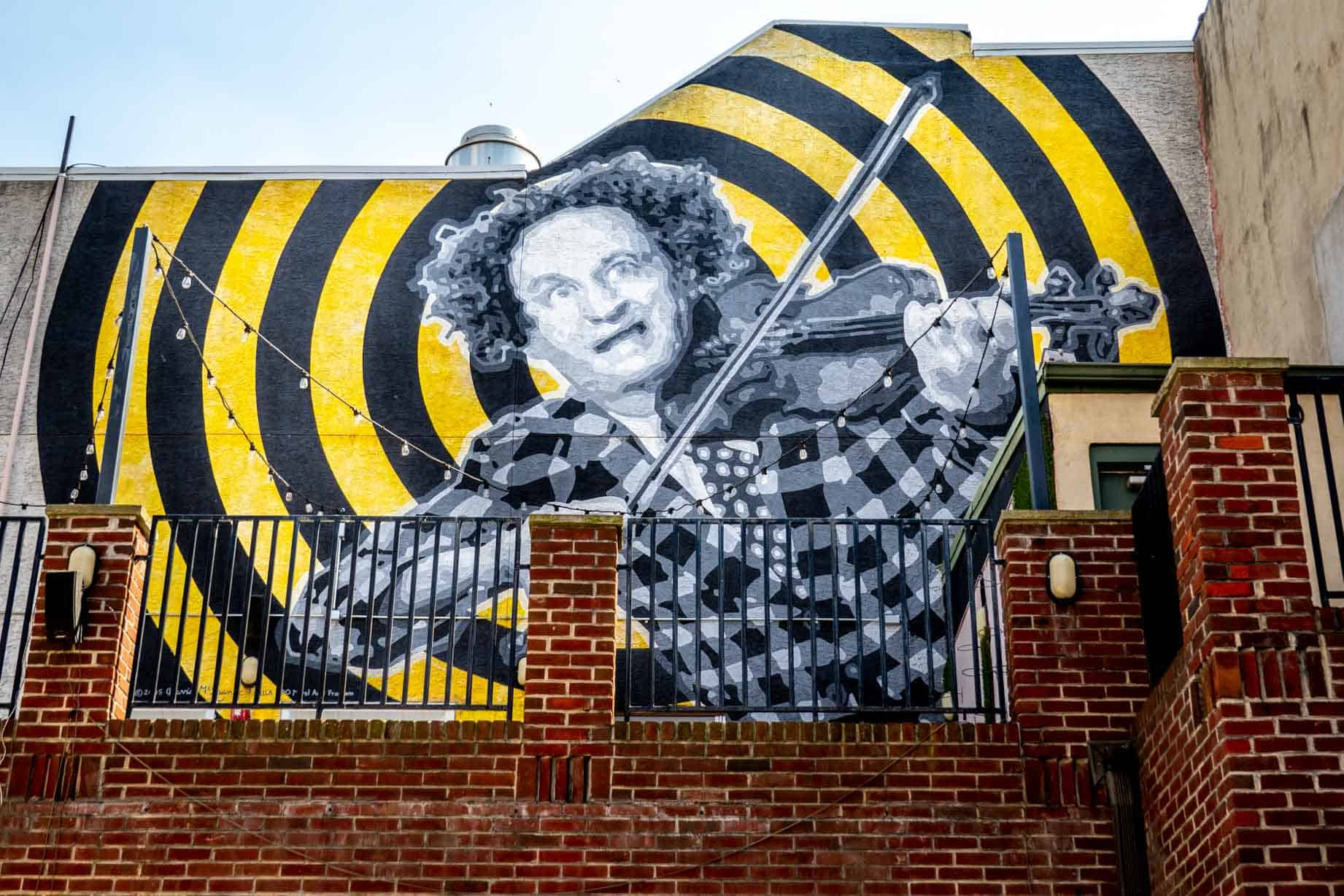 Mural of Larry Fine playing violin on wall on South Street above his boyhood home