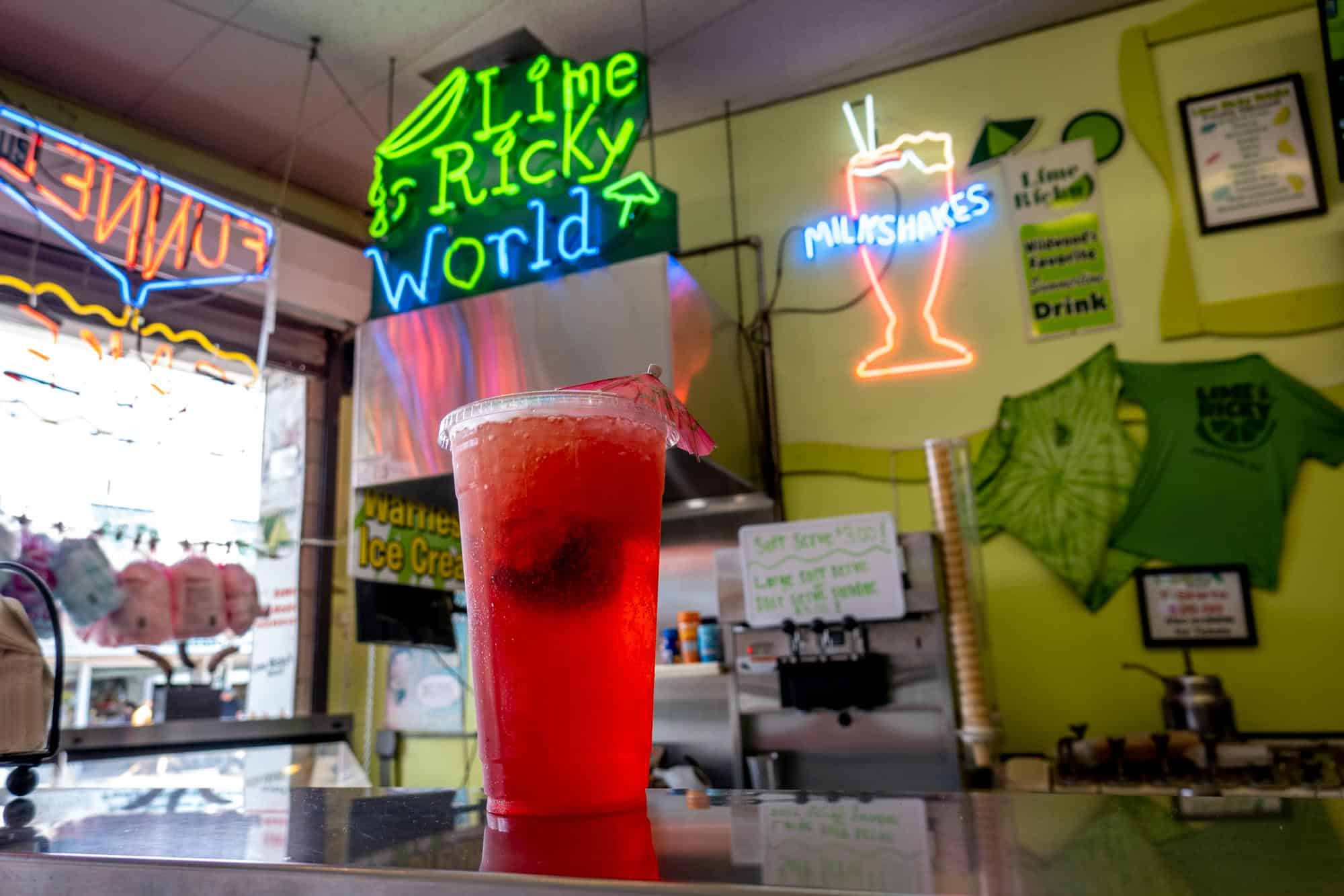 """Red drink on counter in front of neo sign saying """"Lime Ricky World"""""""