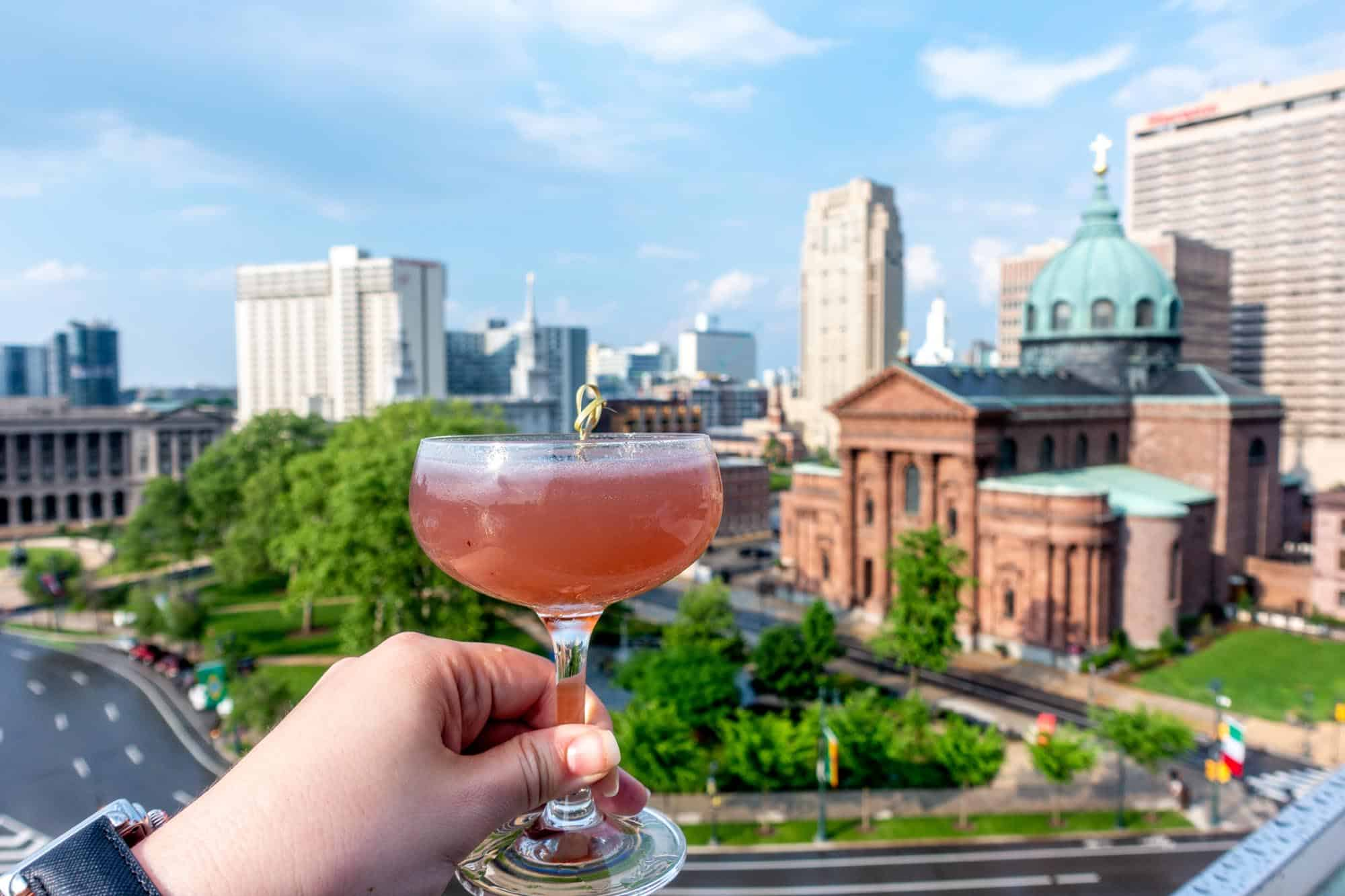 Hand holding a cocktail glass in front of a view of a park and ornate building below
