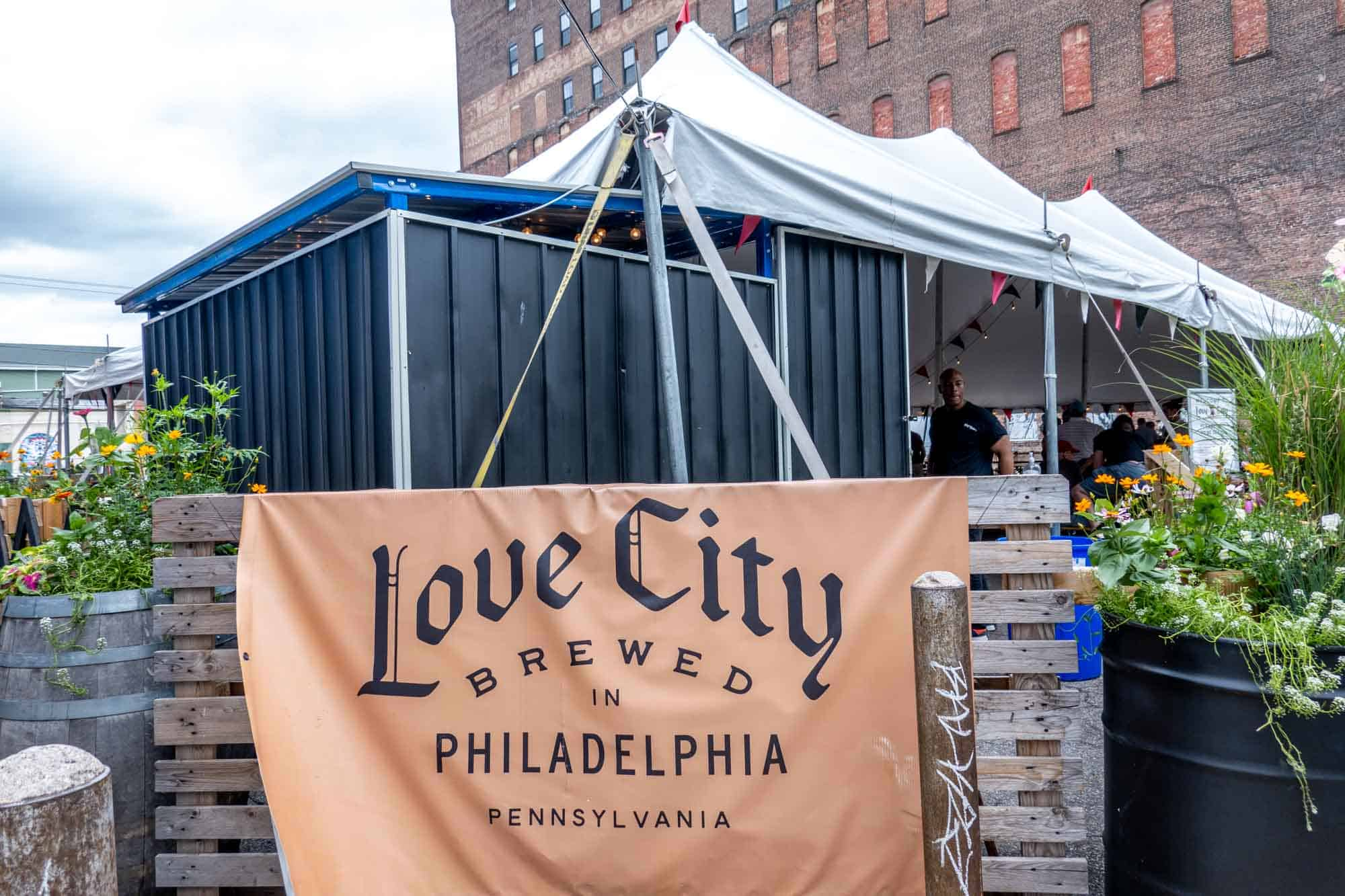 """Sign reading """"Love City Brewed in Philadelphia Pennsylvania"""" in front of garden space"""