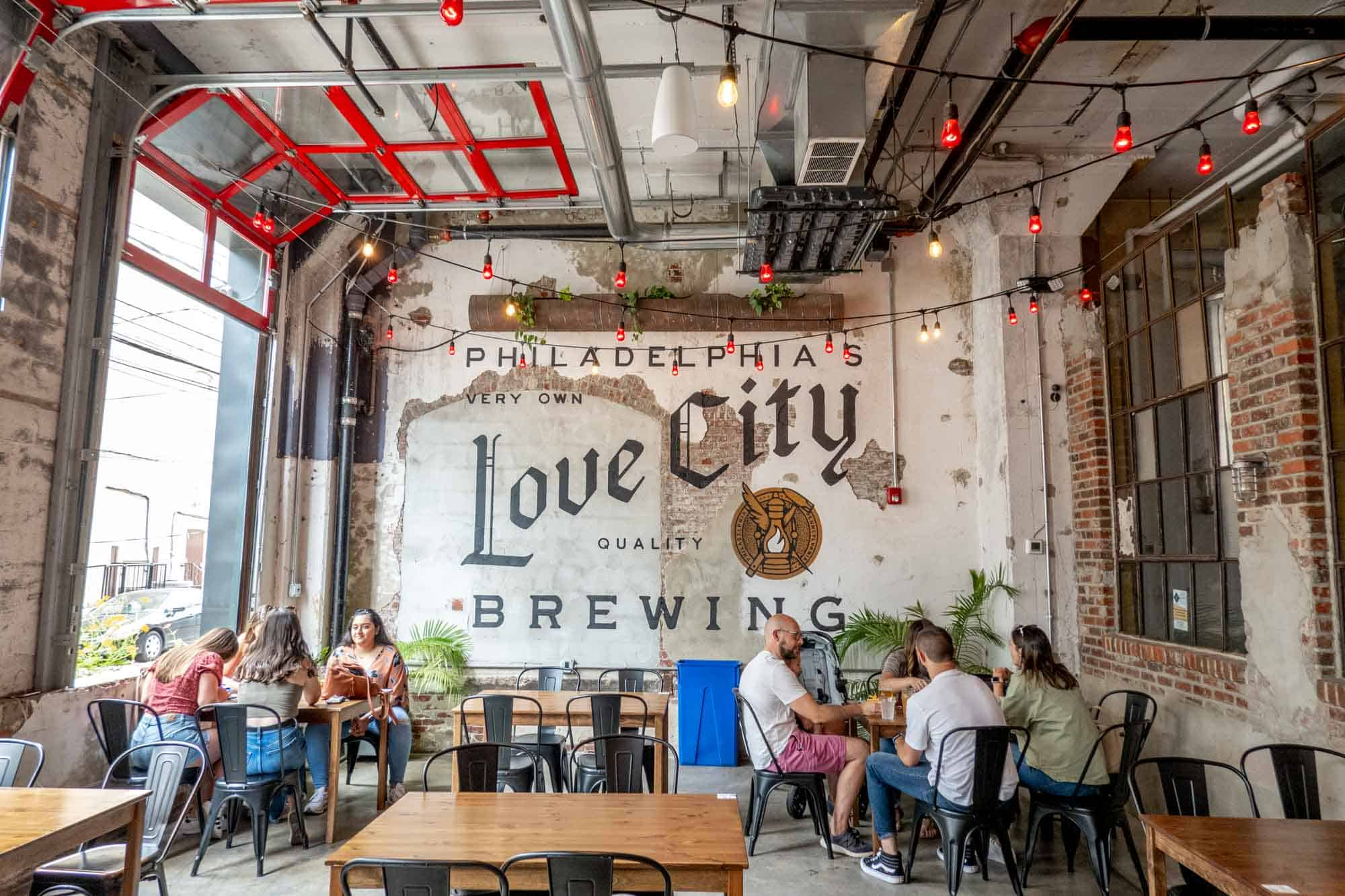 """Mural saying """"Philadelphia's very own Love City quality brewing"""" with people at tables"""