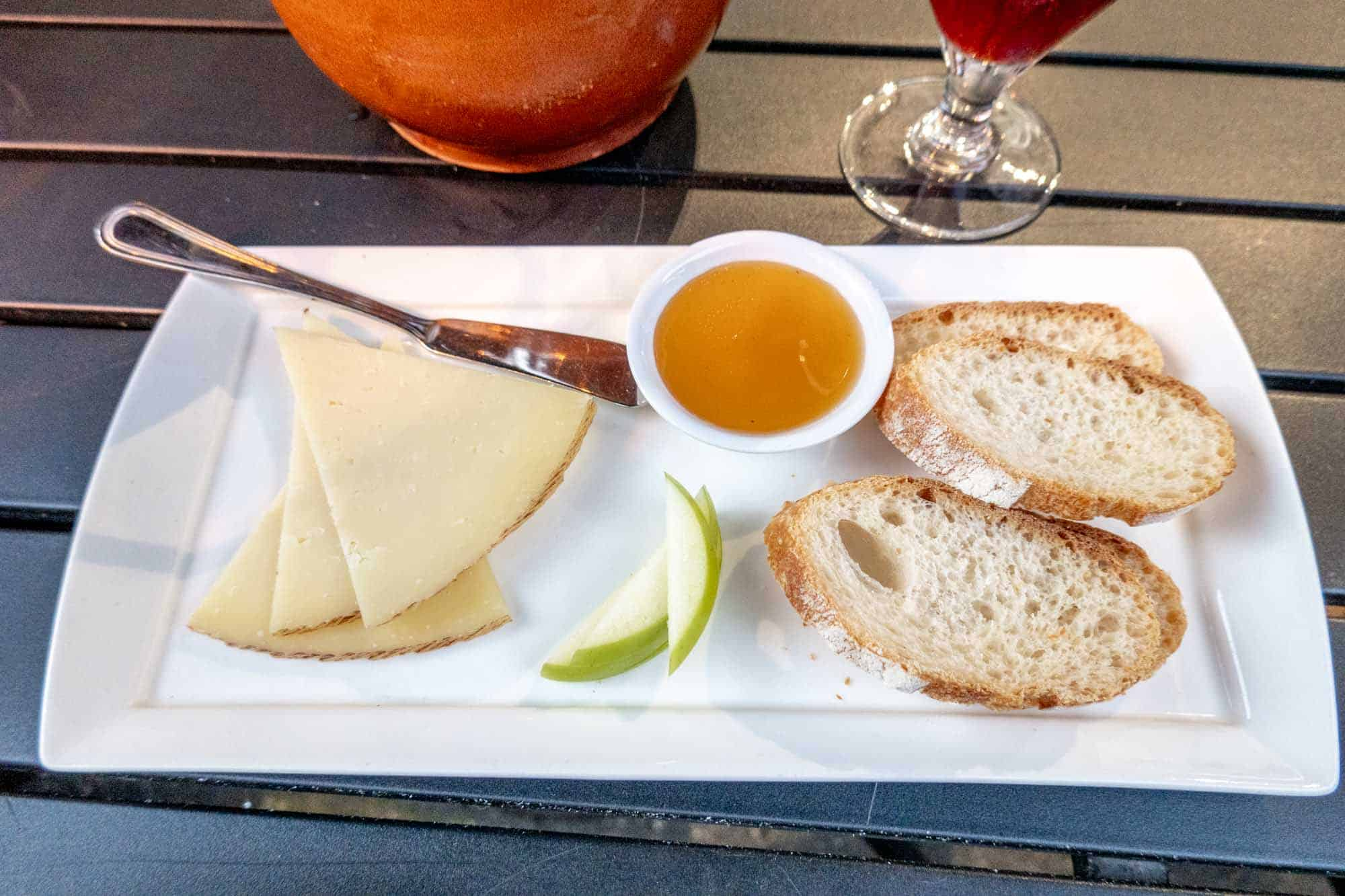 Cheese plate with honey, apple slices and bread