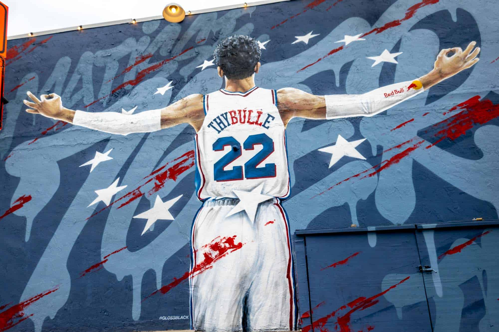 Mural of basketball player Matisse Thybulle with arms outstretched