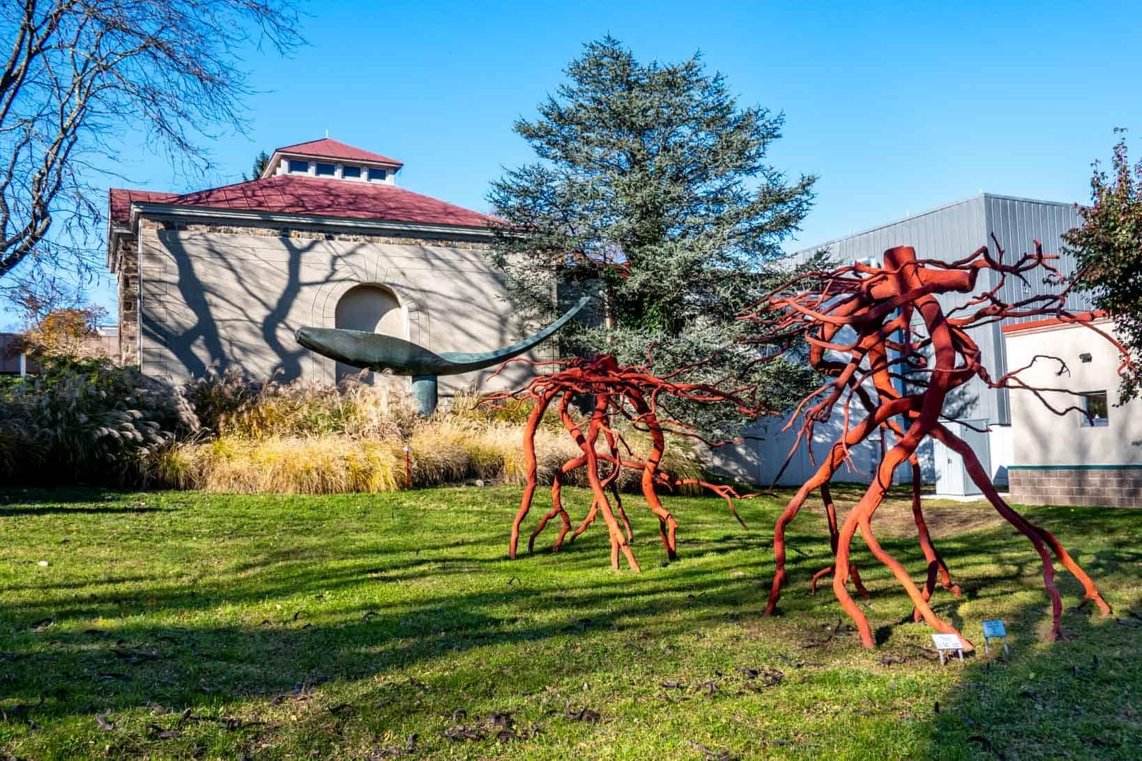 Red, branch-like sculptures in a sculpture garden outside an art museum