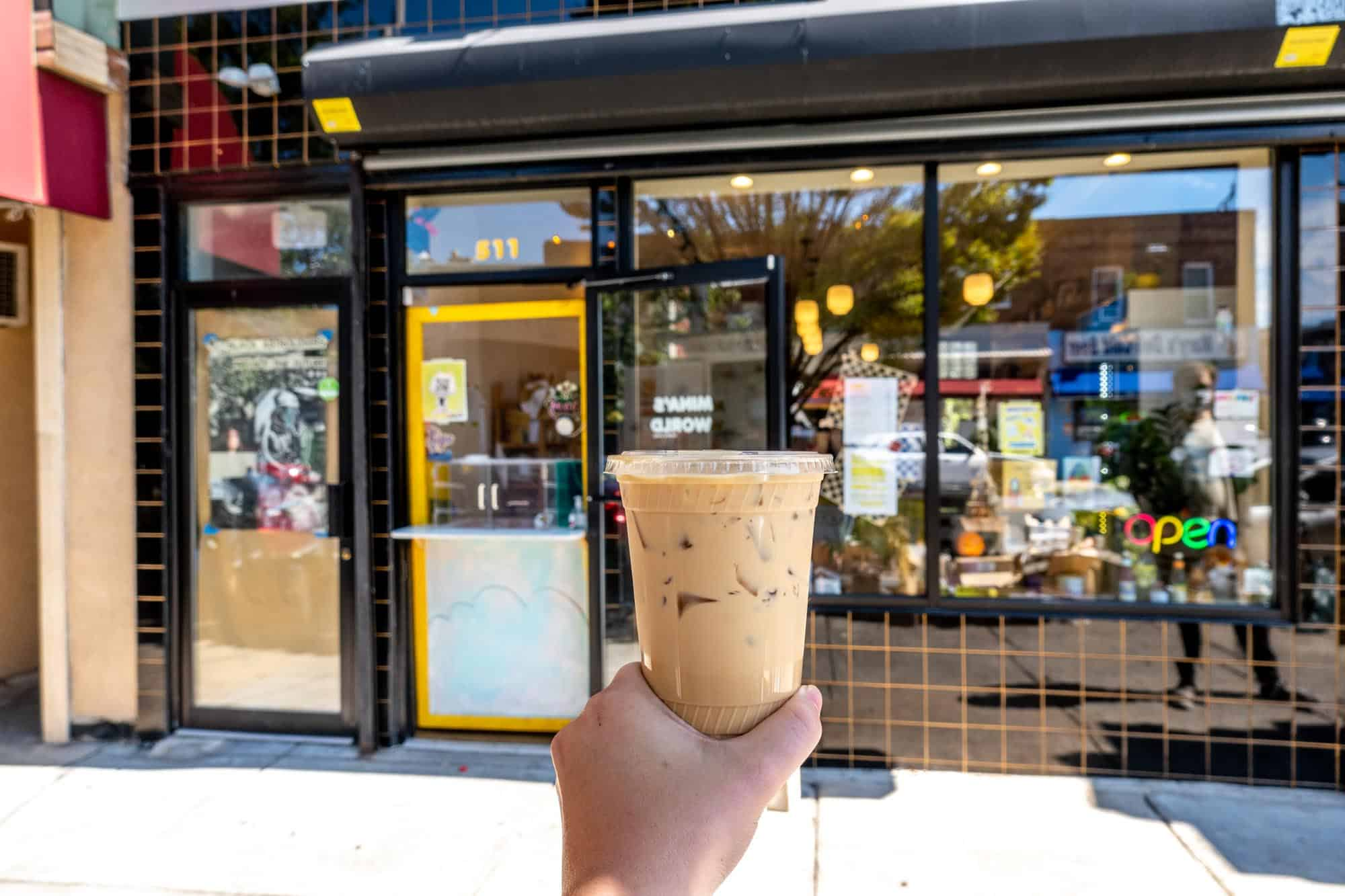 Hand holding a cup of iced coffee in front of a black storefront