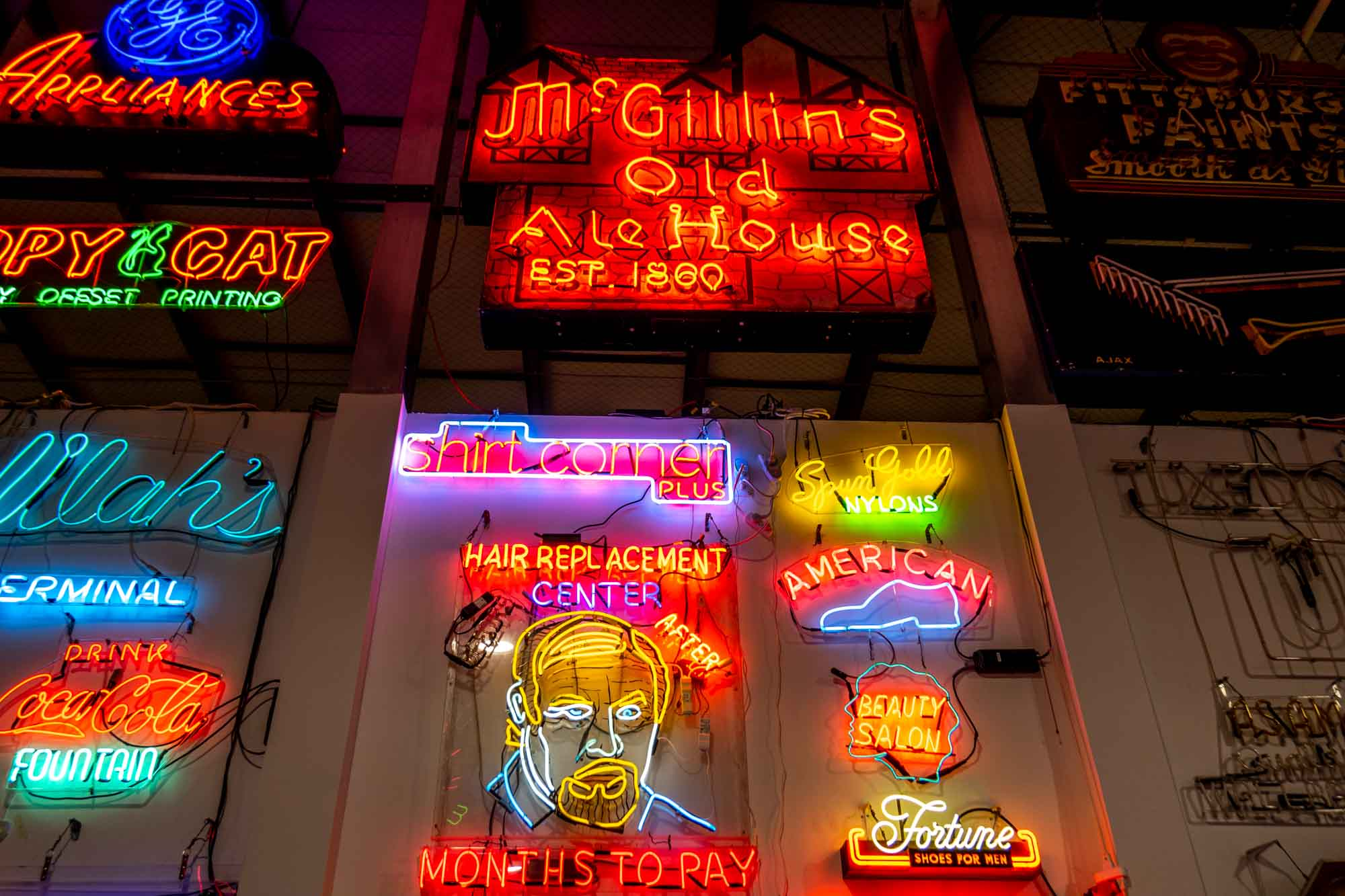 """Lit up neon signs on a wall, including """"McGillin's Old Ale House, Est. 1860,"""" the outline of a shoe, and a man's face advertising Hair Replacement Center"""