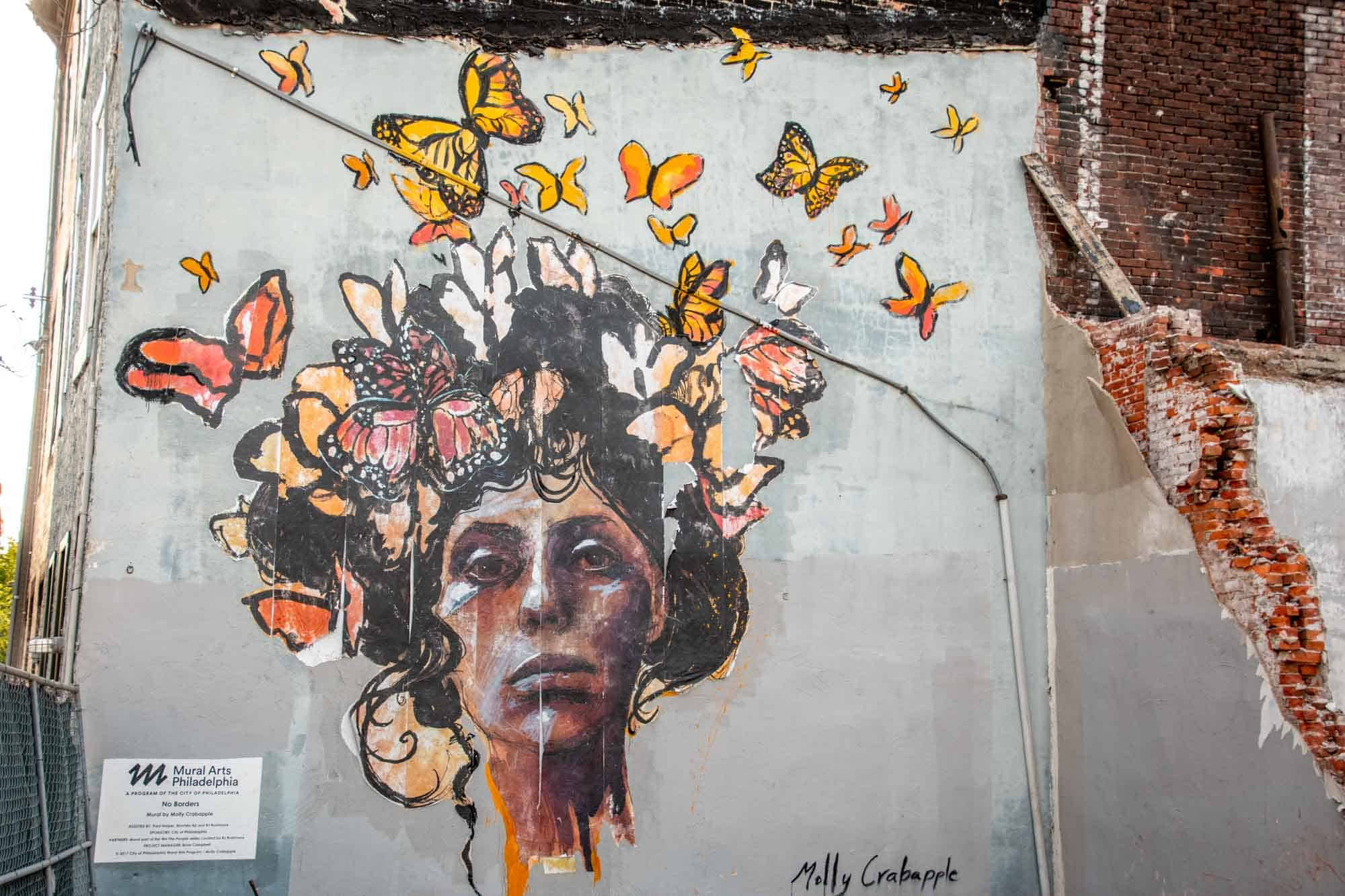 Mural of woman's face with butterflies around her head